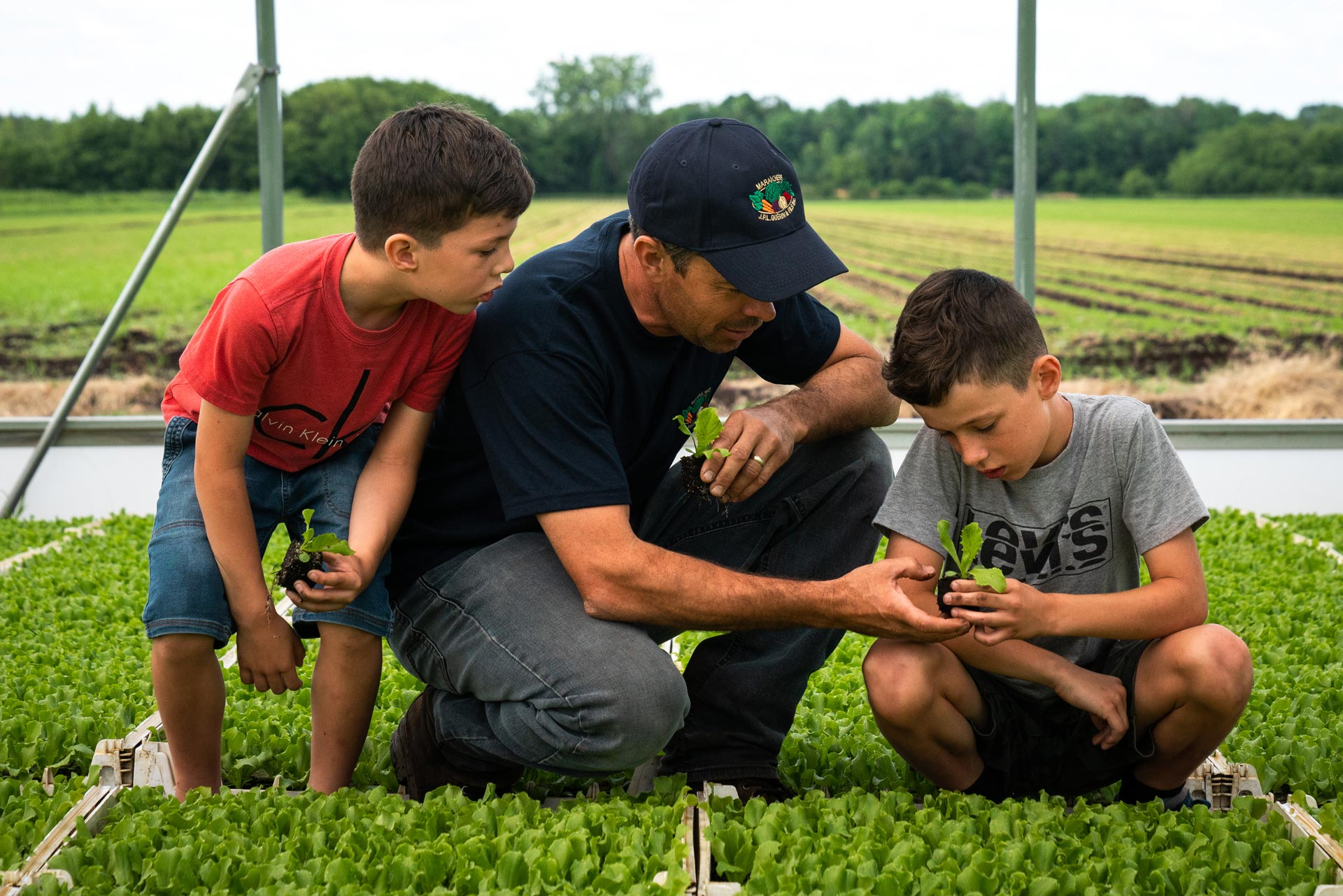 dad and his two sons checking out young plants by Bruno Florin