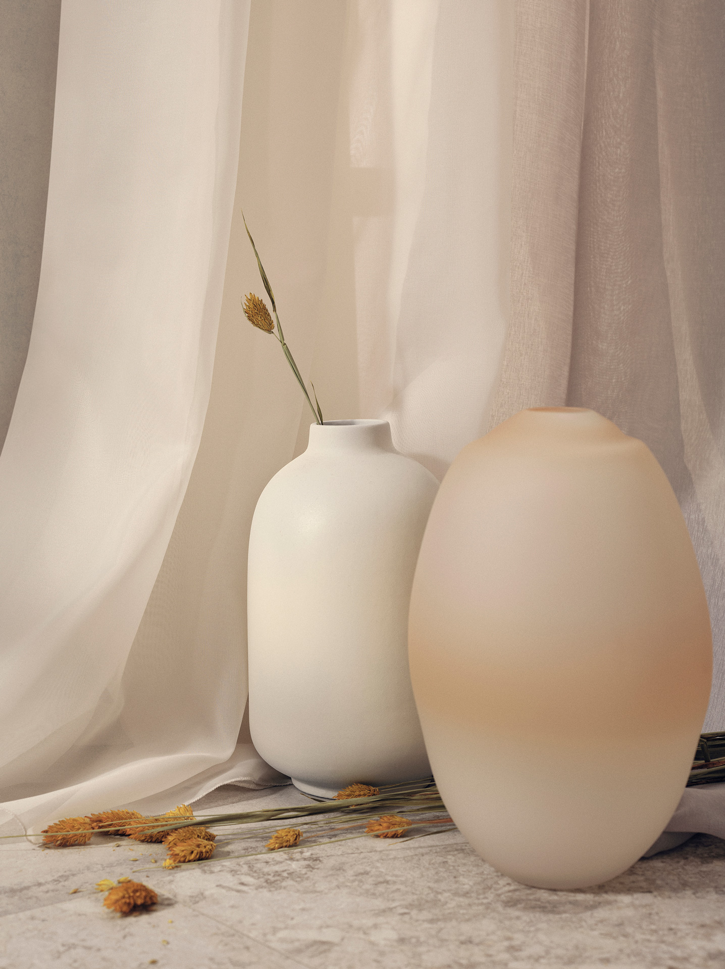 two white vases with single branches inside them against white curtains