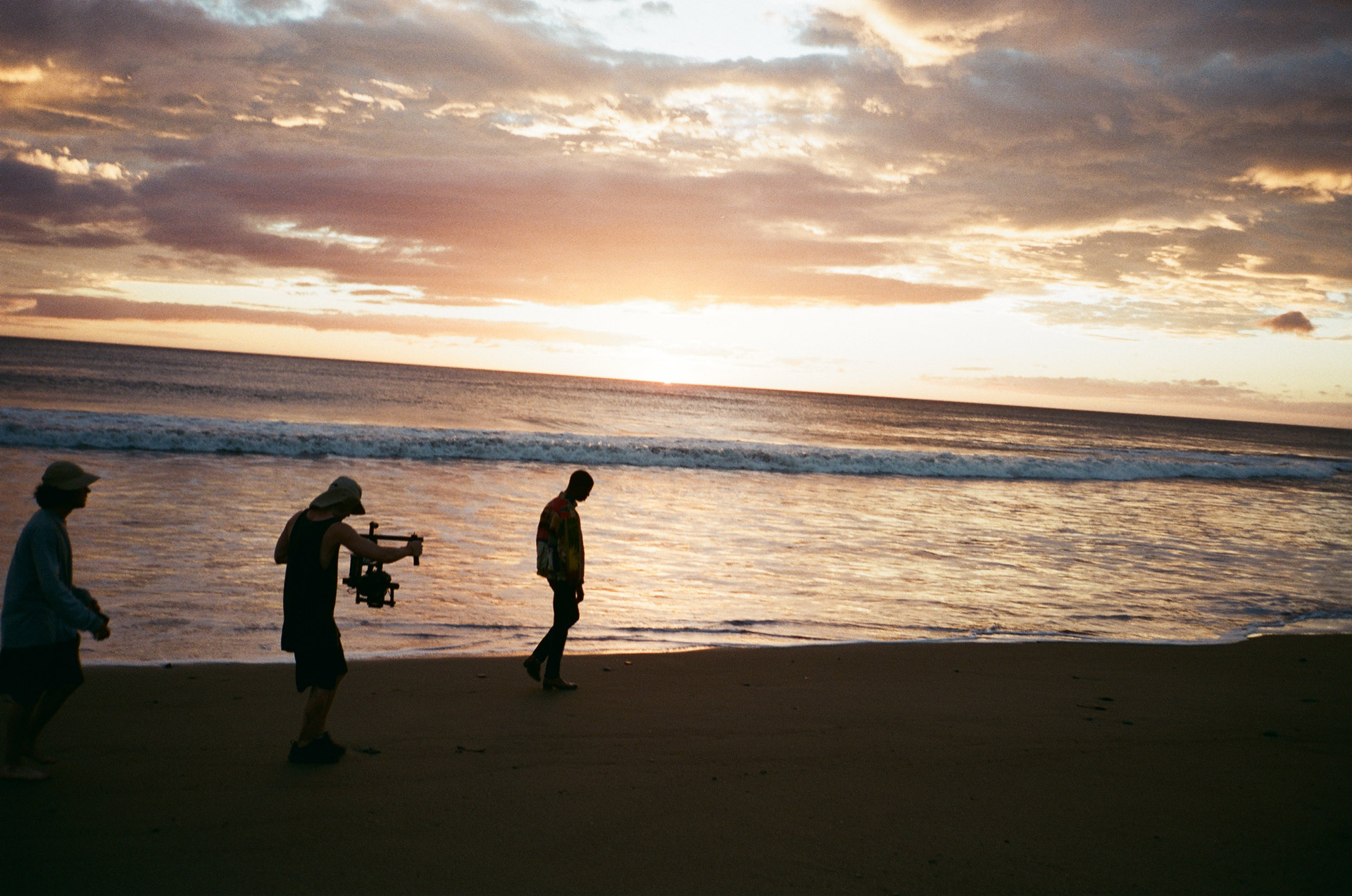 Vincent Ruel-Cote from Les Gamins filming singer Karim Ouellet walking on the beach at sunset for music video of La Mer A Boire