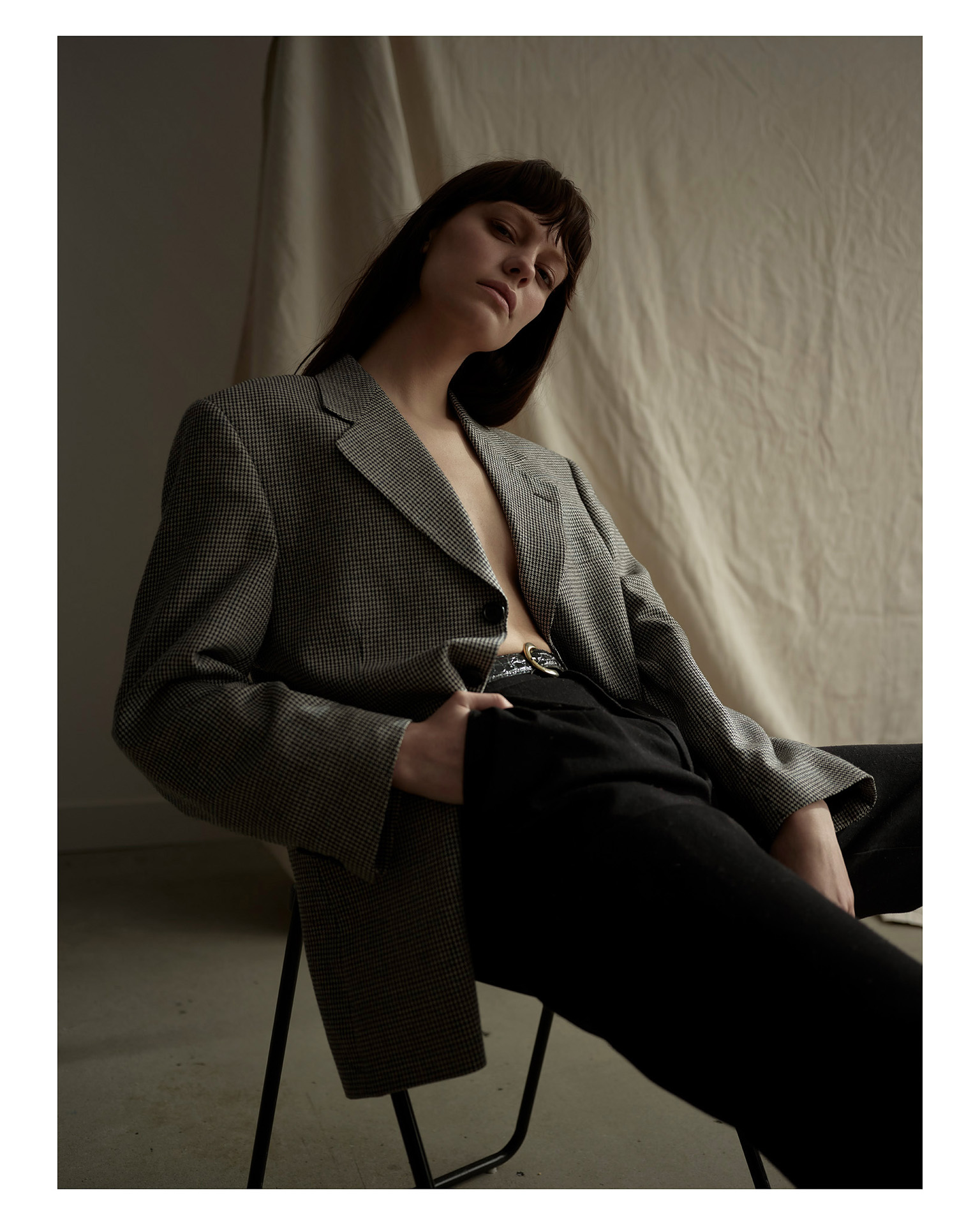 woman sitting on chair wearing black suit pants and checkered oversized suit jacket hand in her pocket leaning back looking at camera by Maxyme G Delisle for Mariane