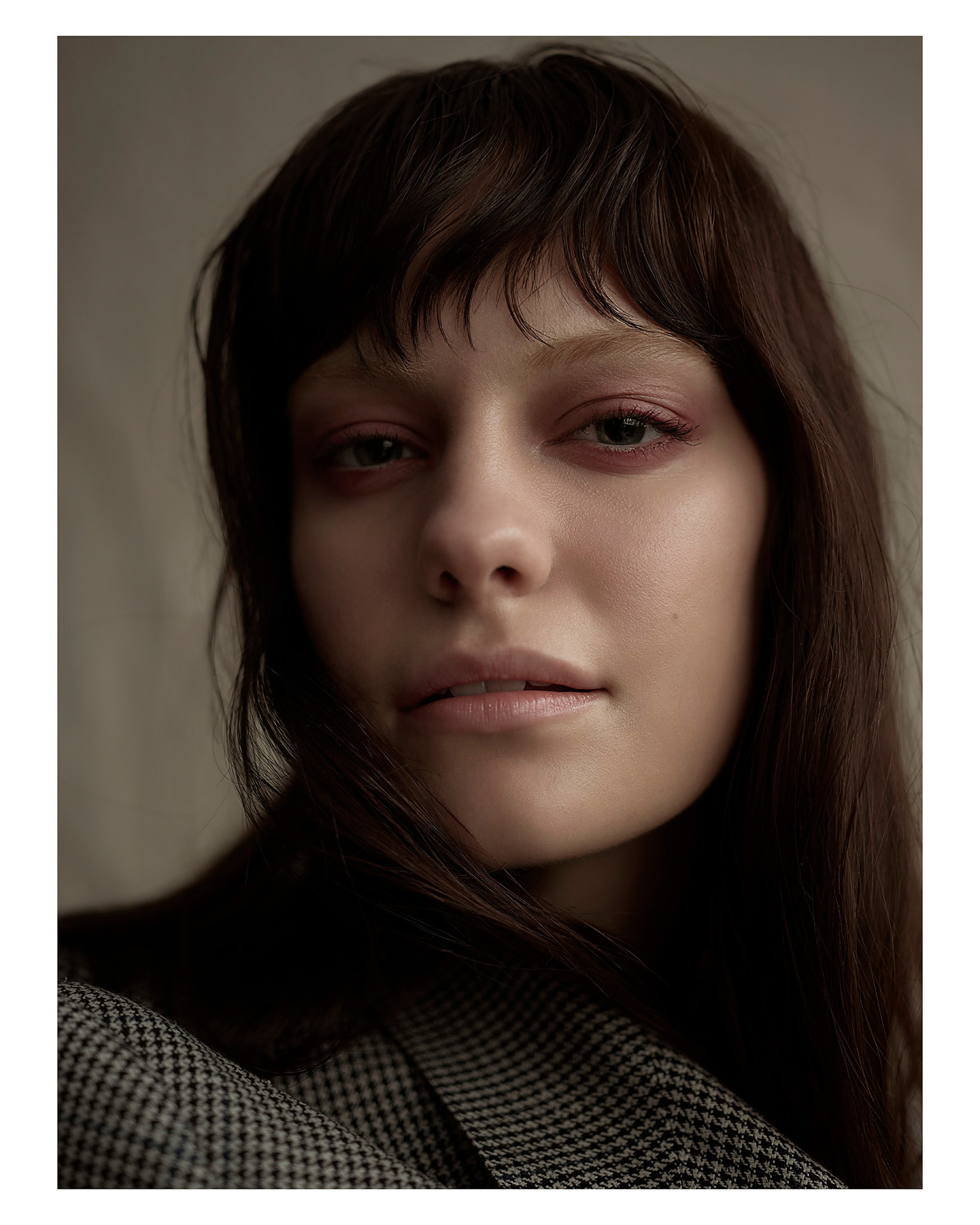 close up shot of woman model face looking at camera wearing soft pink makeup and checkered oversized suit jacket by Maxyme G Delisle for Mariane