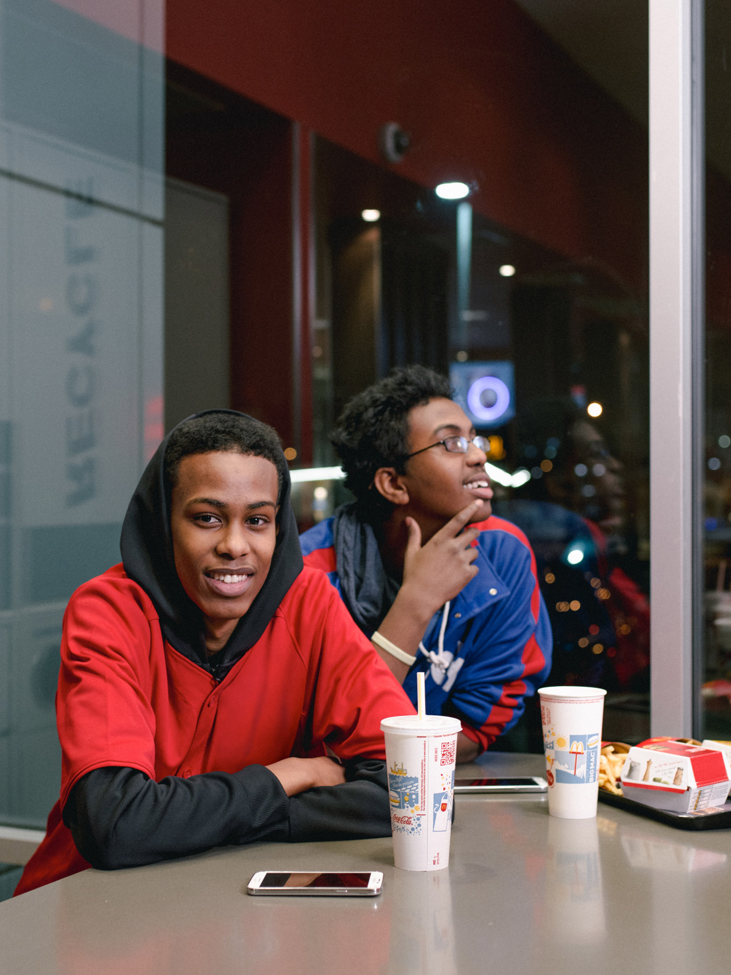 two young black men sitting at table with drinks and fries looking at camera by Alexi Hobbs for McDonald's