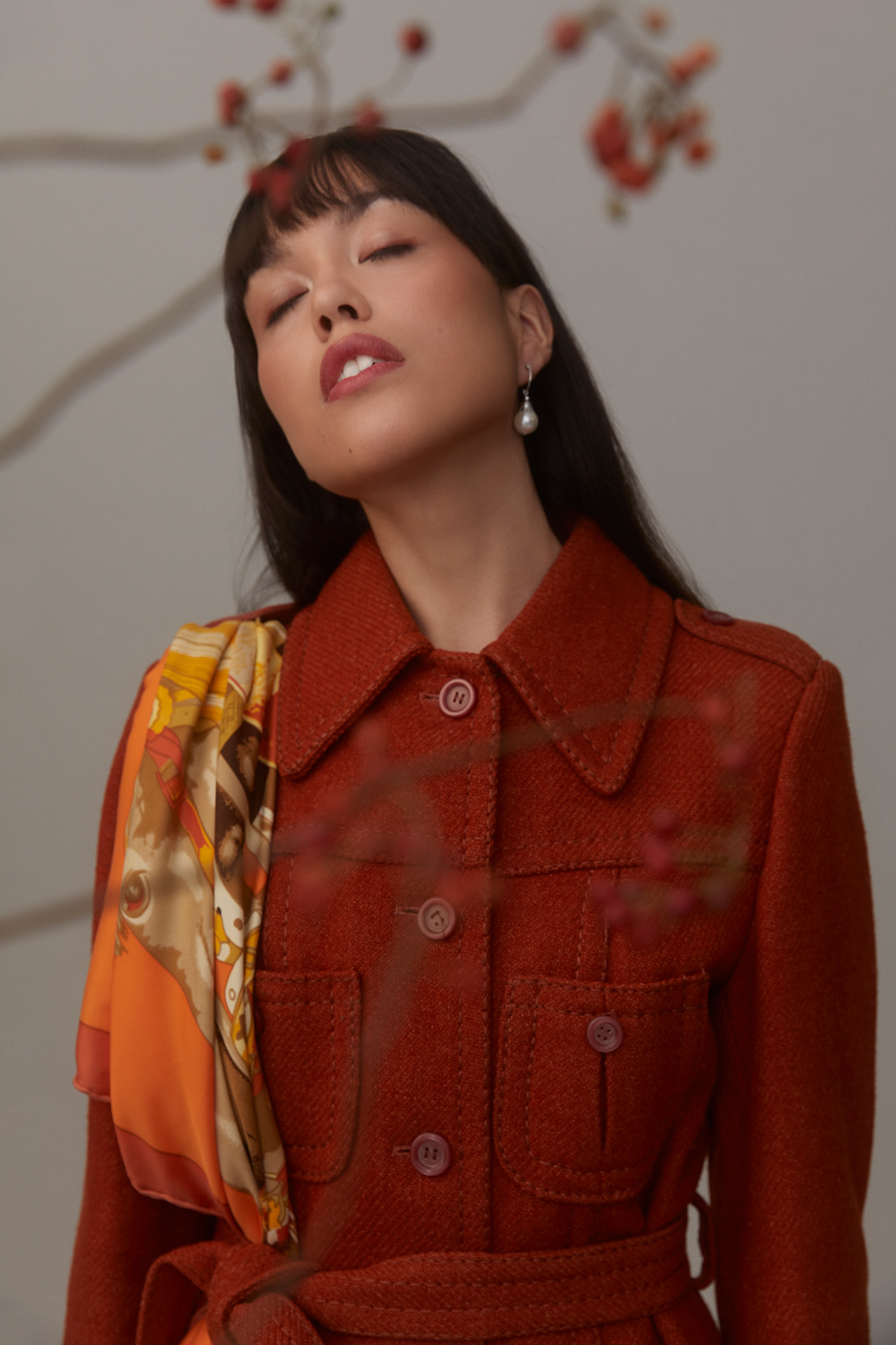 female model wearing red trench coat standing eyes closed with blurred branches of red fruits in the foreground photographed by Kelly Jacob for LEV