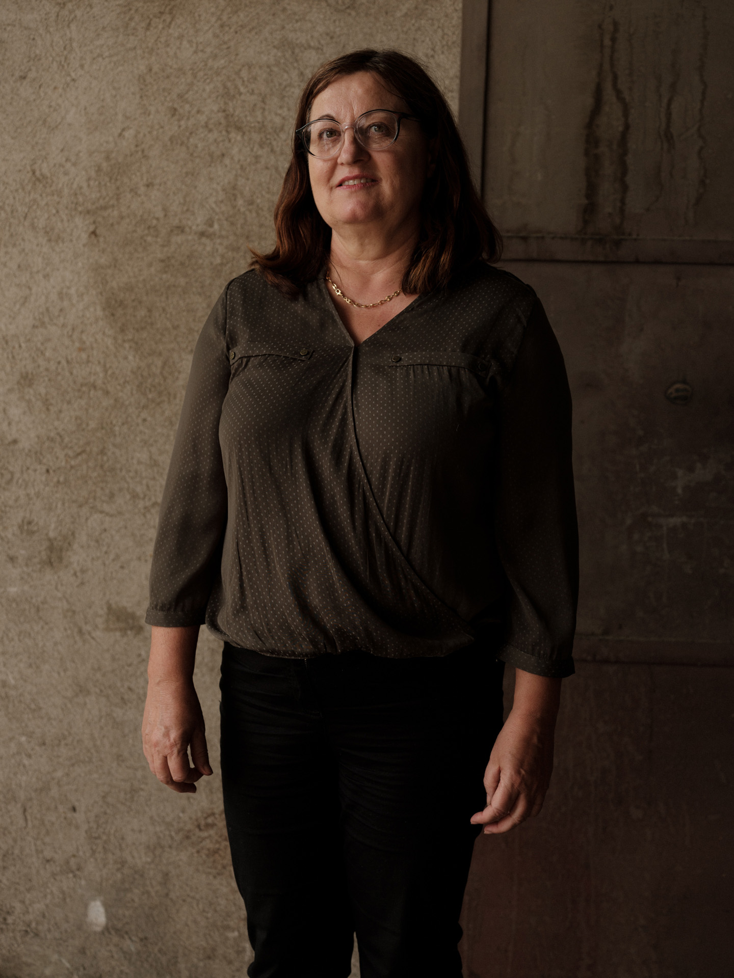 portrait of lady in front of concrete wall dressed in brown by Alexi Hobbs in Auvergne for Reflets de France
