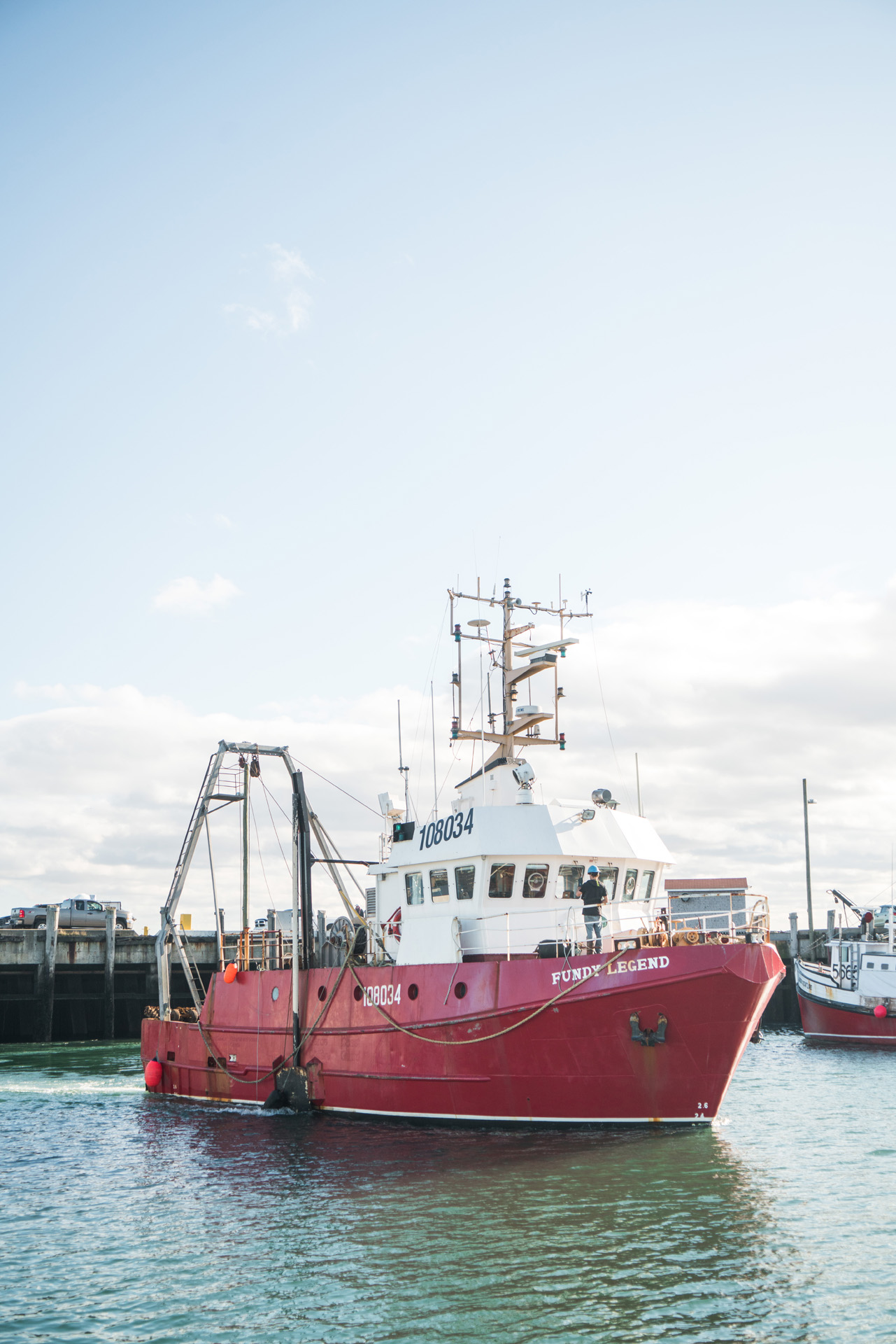 red fishing boat in the port by Bruno Florin for Ricardo Magazine in Bay of Fundy
