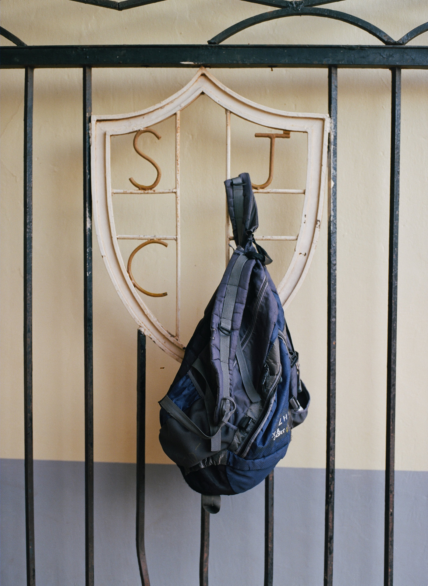 beaten up dark blue backpack hanging on metal fence with monogram by Alexi Hobbs in Uganda for Football for Good with Sportsnet