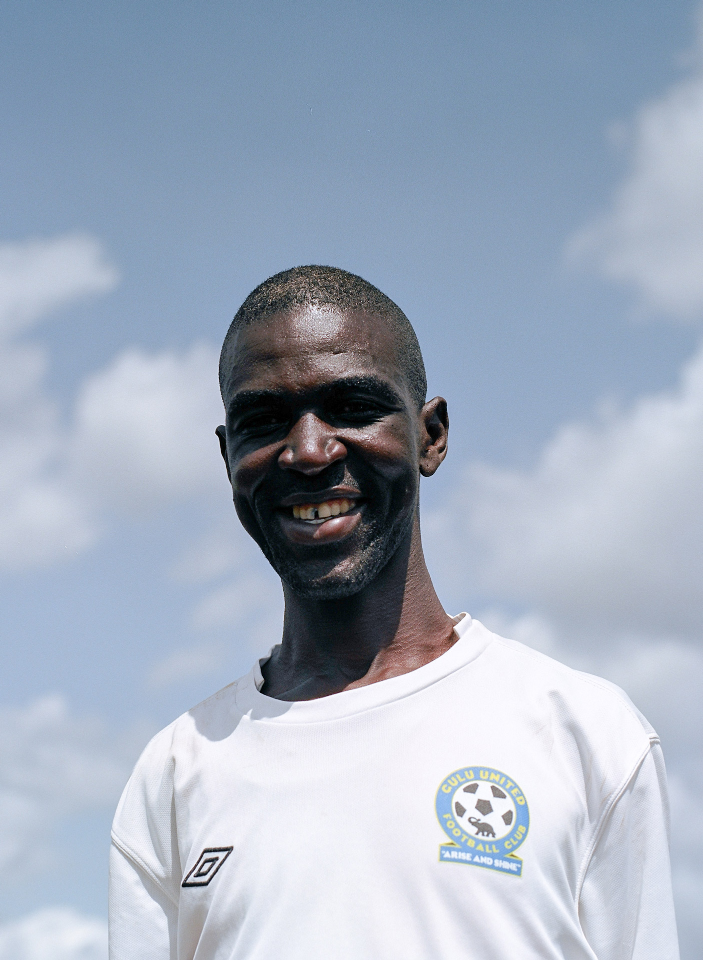 portrait of black man wearing white shirt smiling at camera with blue sky in the background by Alexi Hobbs in Uganda for Football for Good with Sportsnet