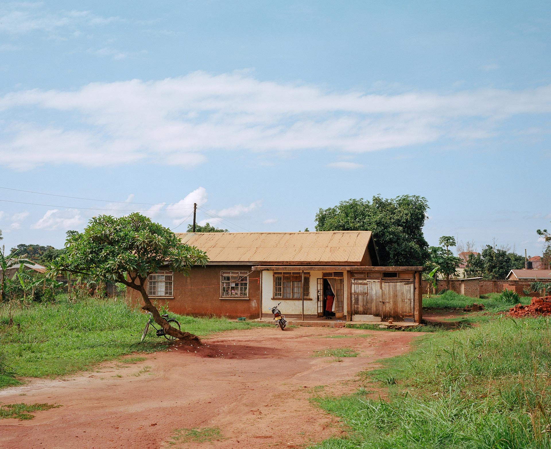 simple brown house made of dirt and metal sheets by Alexi Hobbs in Uganda for Football for Good with Sportsnet