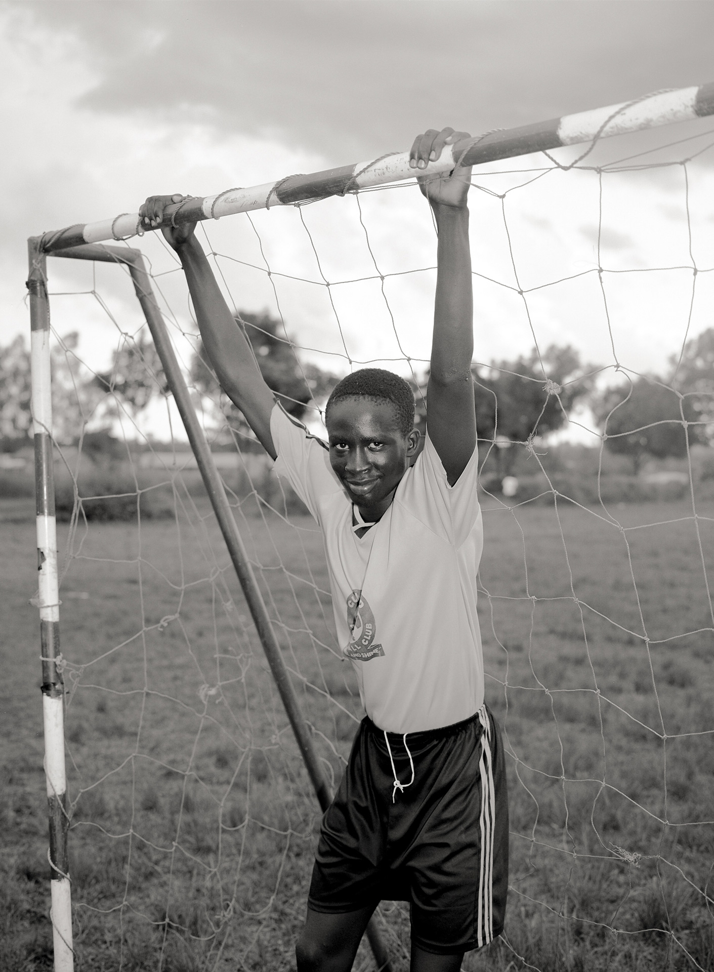 black and white picture of young goalie suspended by the metal frame looking at camera wearing yellow soccer jersey and black sports short by Alexi Hobbs in Uganda for Football for Good with Sportsnet