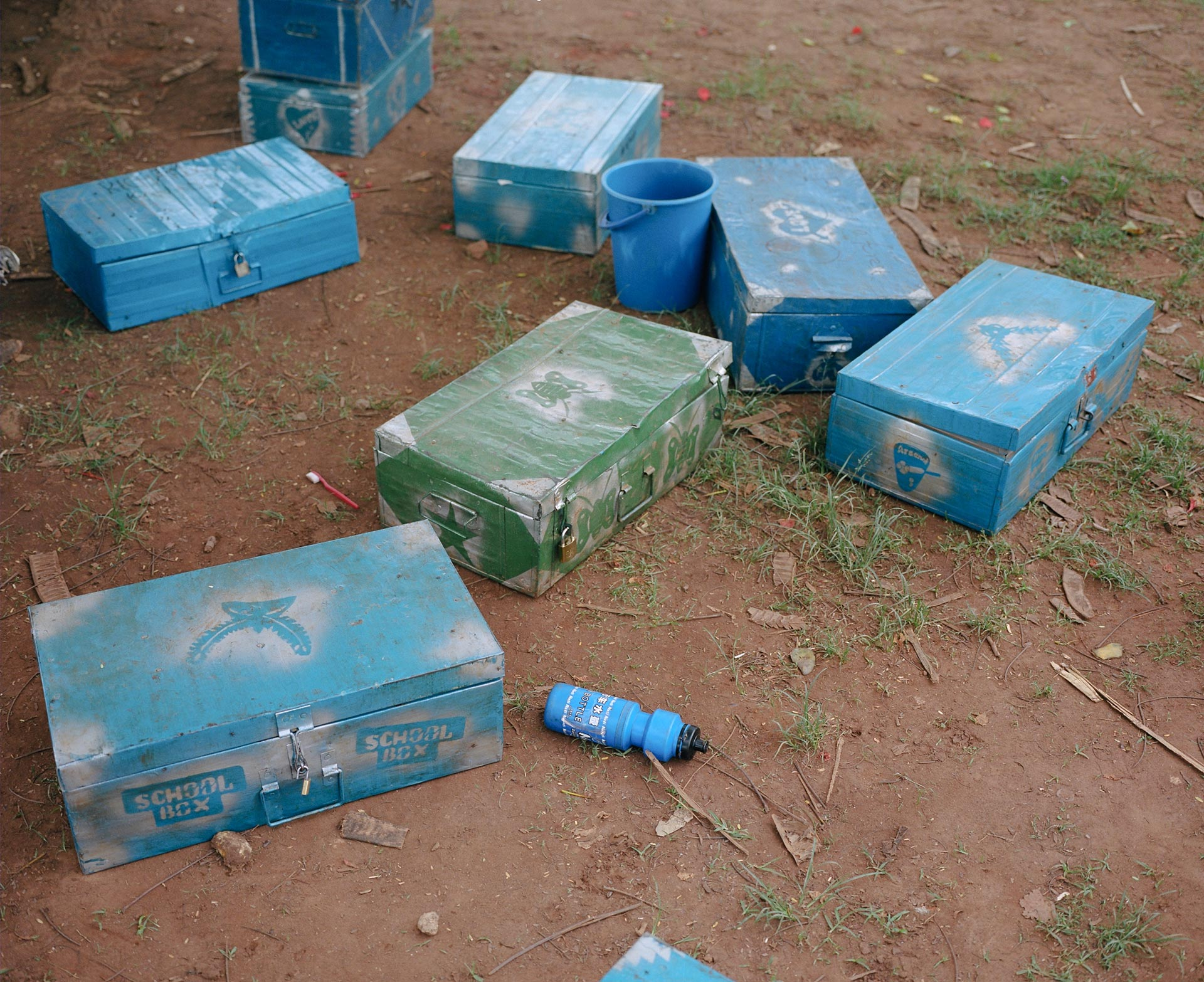 blue metal chests on the ground decorated and labeled school boxes with blue water bottle around by Alexi Hobbs in Uganda for Football for Good with Sportsnet