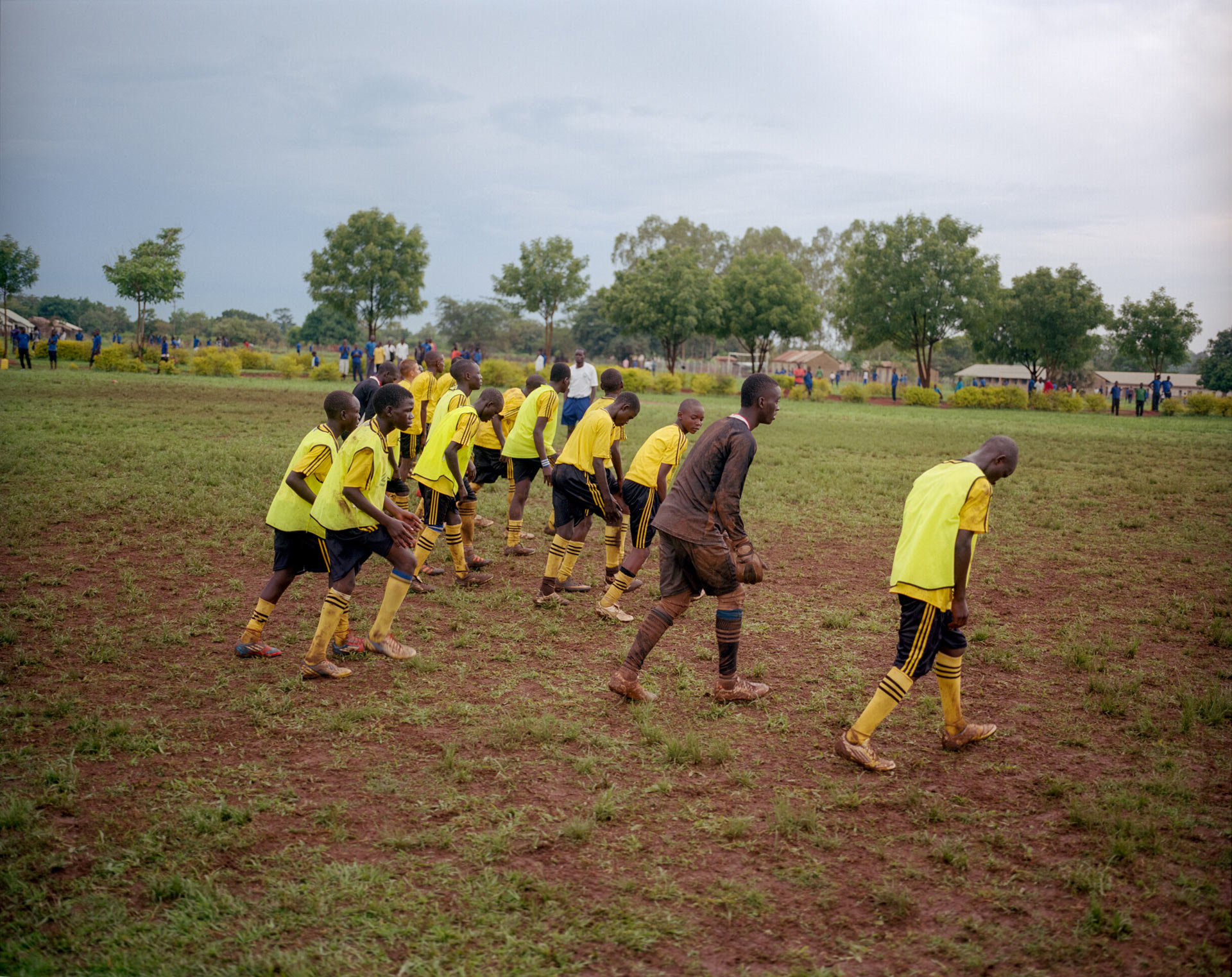 group of young black boys running in line and warming up for match wearing yellow soccer jersey by Alexi Hobbs in Uganda for Football for Good with Sportsnet