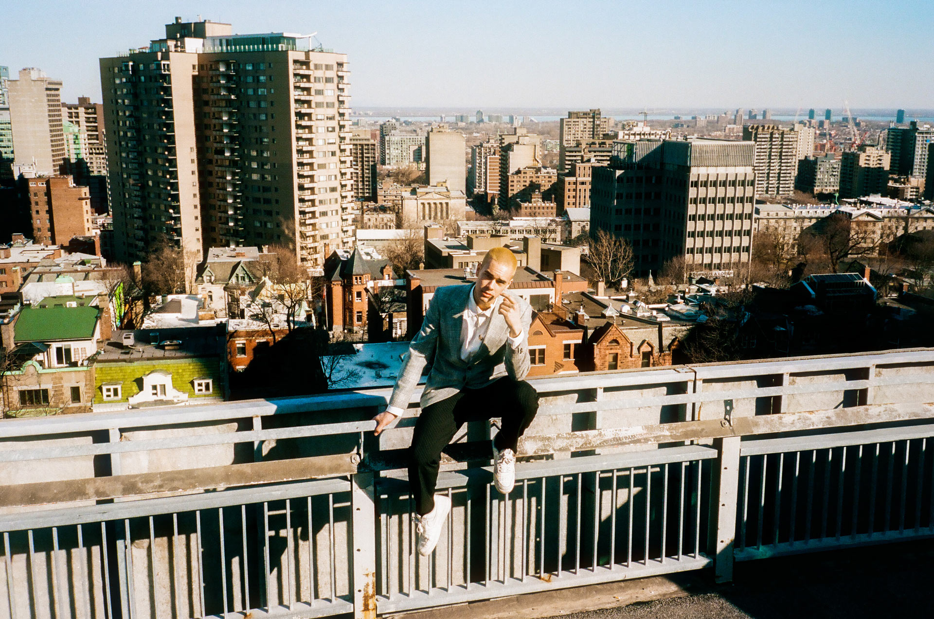 singer Yuki Dreams Again sitting on metal railing looking right at camera with view of the city and buildings in the background in behind the scenes of their promotional video filmed by Les Gamins