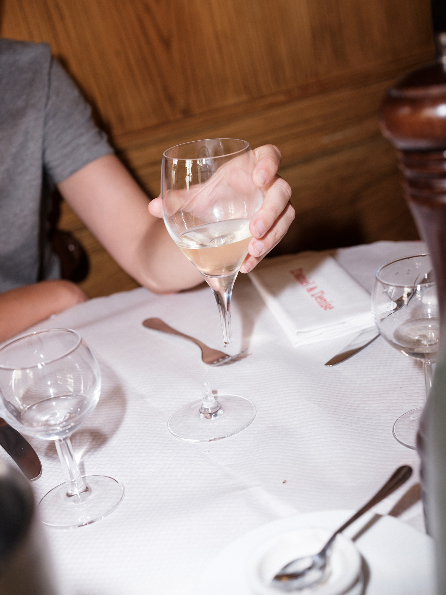man holding glass of white wine in restaurant by Alexi Hobbs in Auvergne for Reflets de France