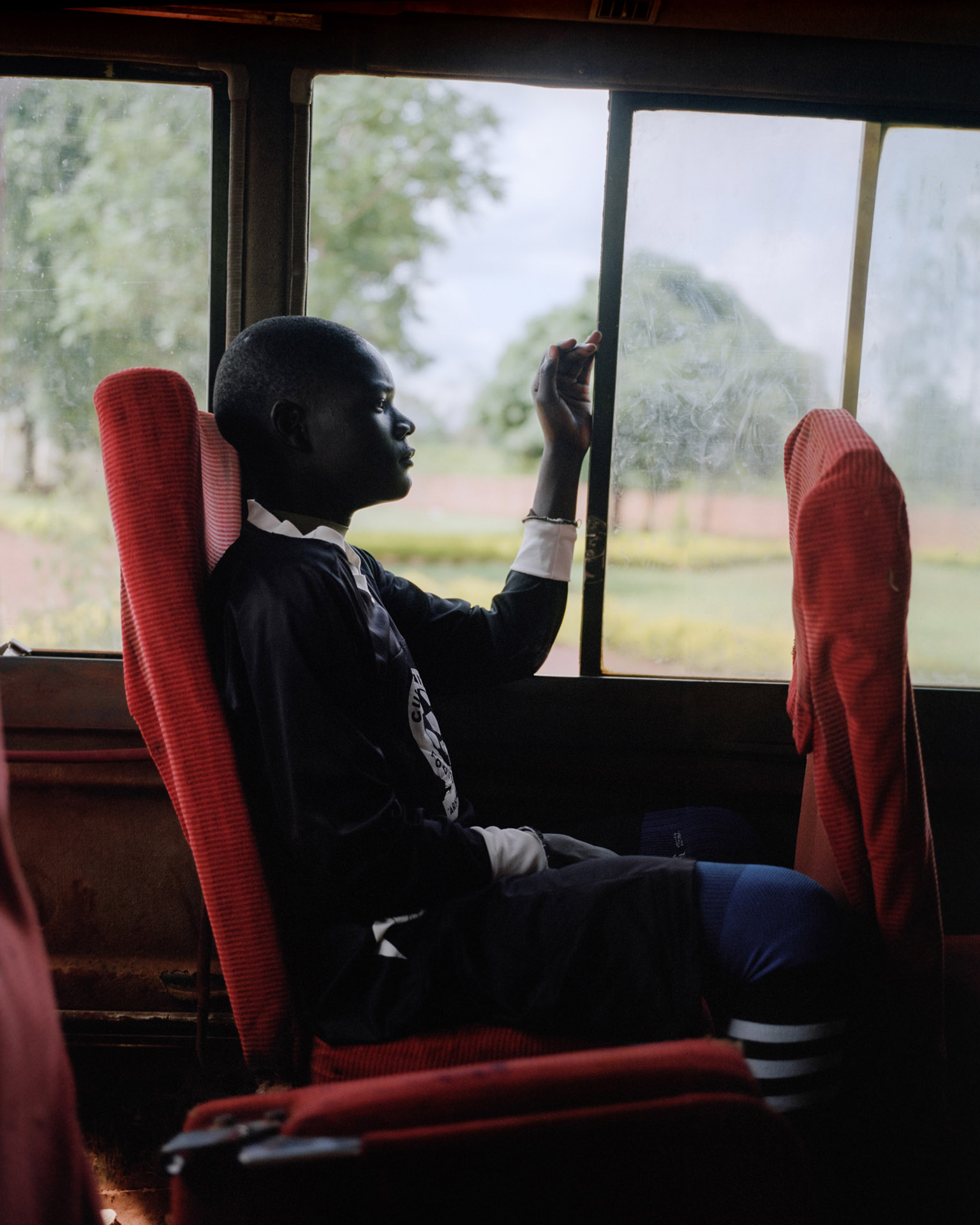 young black boy in bus looking outside by Alexi Hobbs in Uganda for Football for good with Sportsnet