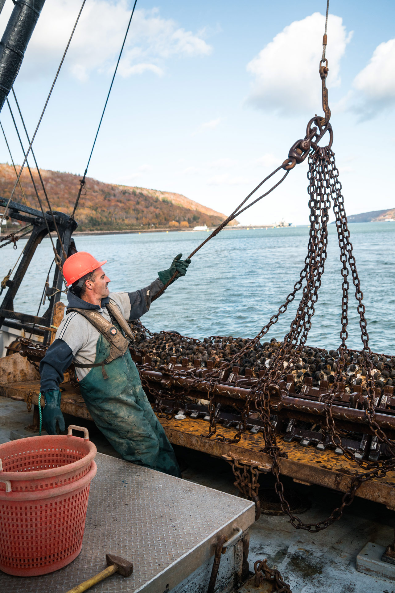 fisherman wearing red helmet stirring the fishing platform by Bruno Florin for Ricardo Magazine in Bay of Fundy