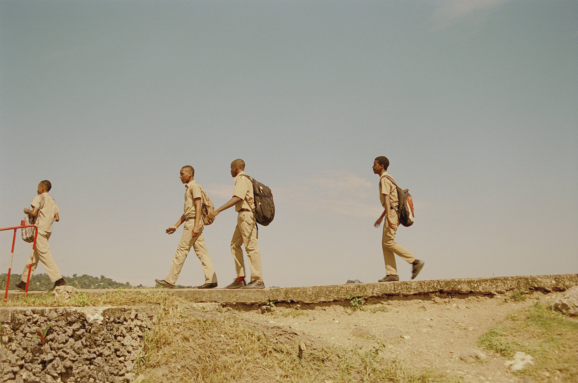 young jamaican students in uniform with their bags going back home by Oumayma B Tanfous in Jamaica