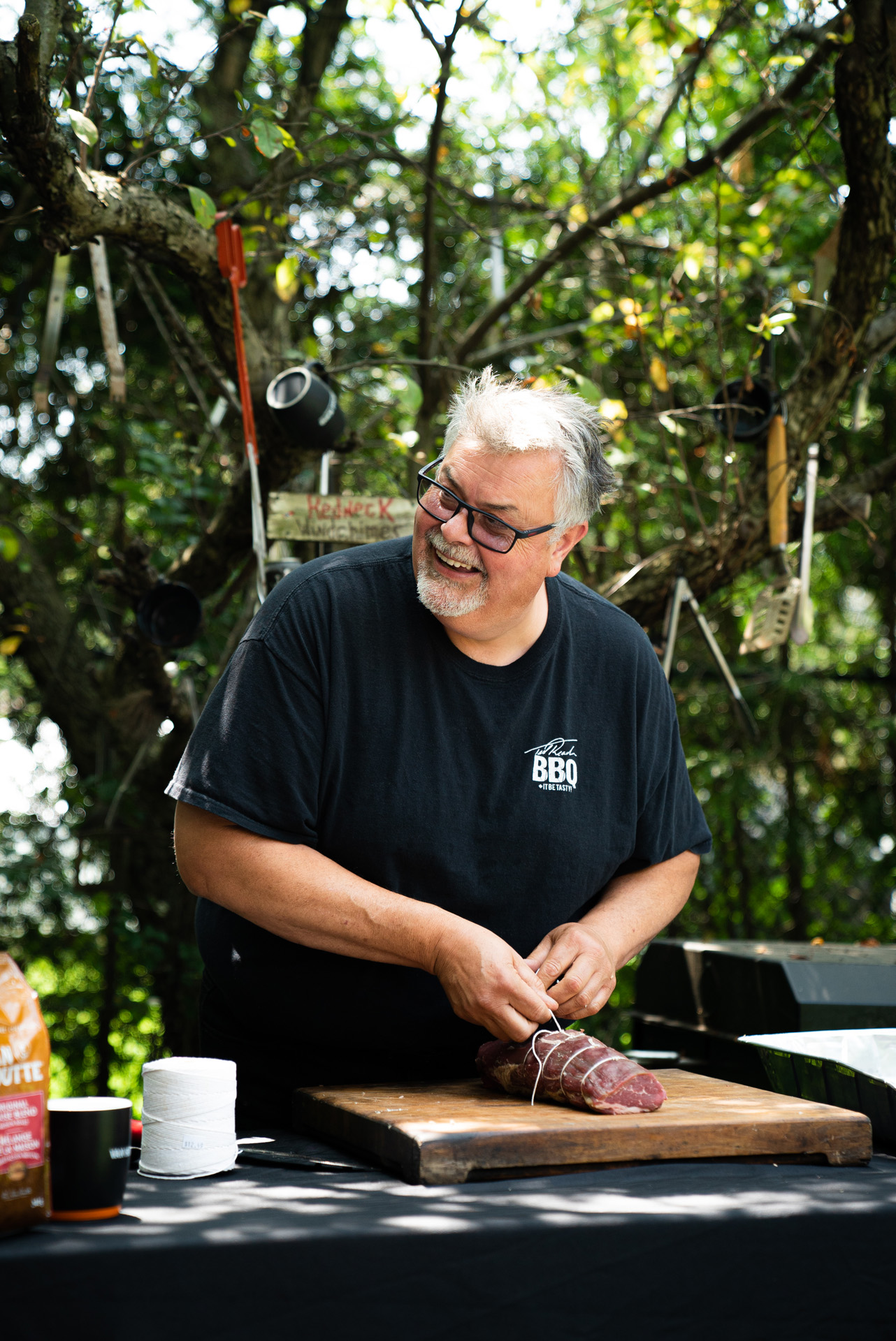 chef Ted Reader tying up a piece of meat with rope cooking outside by Bruno Florin for Van Houtte 100th anniversary