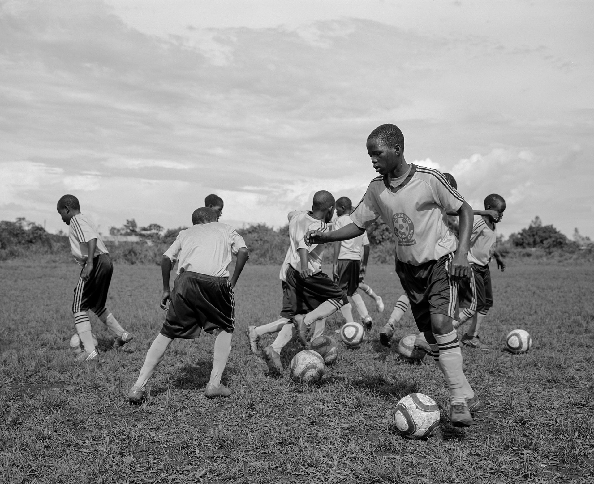 young black soccer players practicing their kicks in black and white by Alexi Hobbs in Uganda for Football for good with Sportsnet