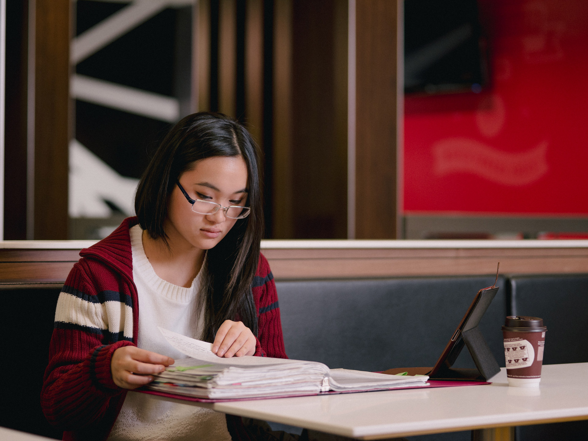 young asian girl sitting at table studying a huge binder with tablet beside her by Alexi Hobbs for McDonald's