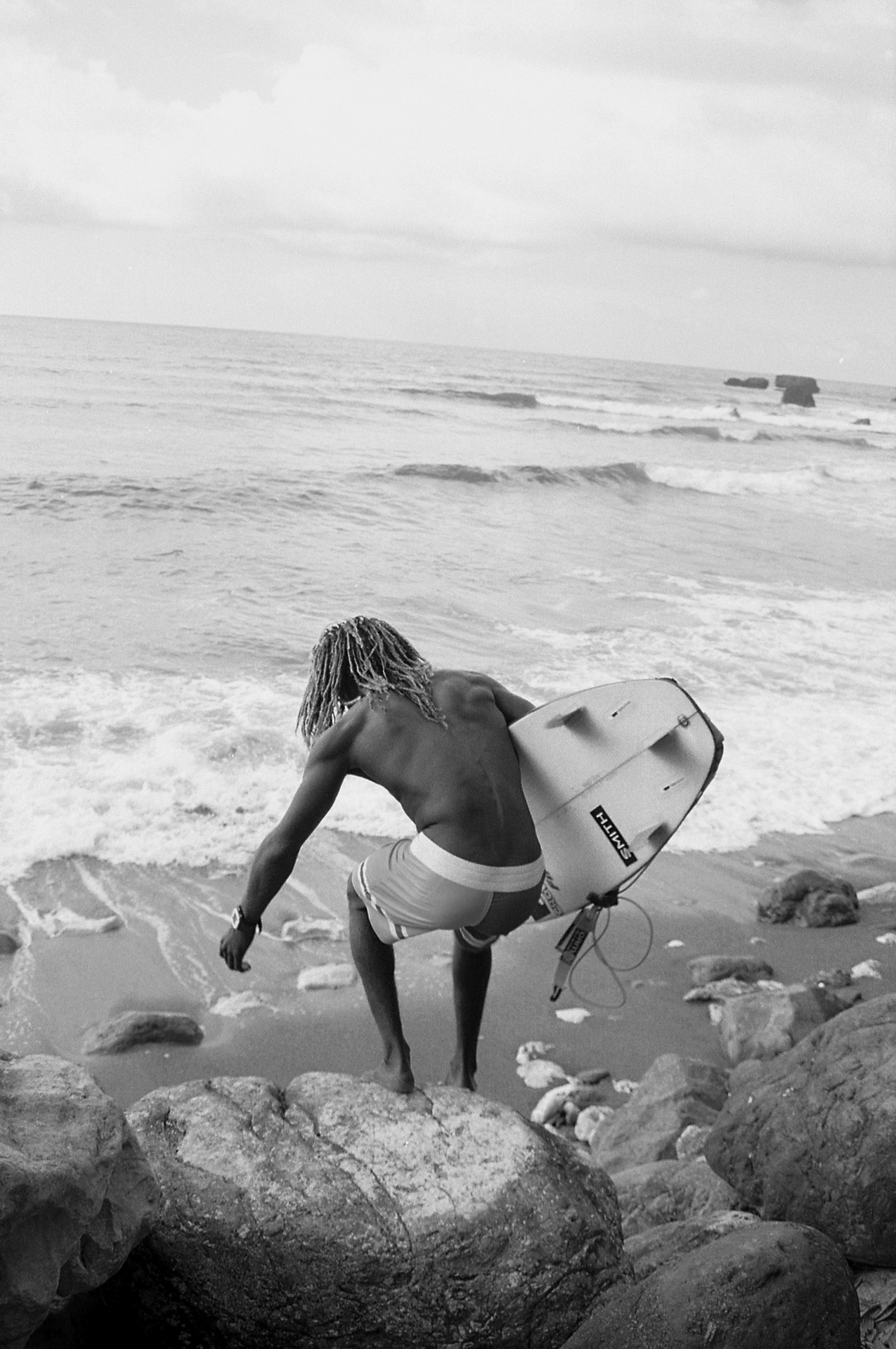 young jamaican surfer with dreadlocks getting down from stones to the beach surfboard under his arm by Oumayma B Tanfous in Jamaica