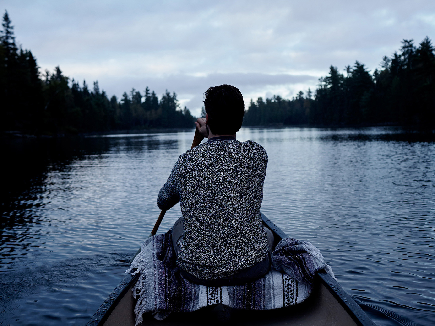 man in a canoe paddling softly on smooth water at dawn by Guillaume Simoneau in Abitibi