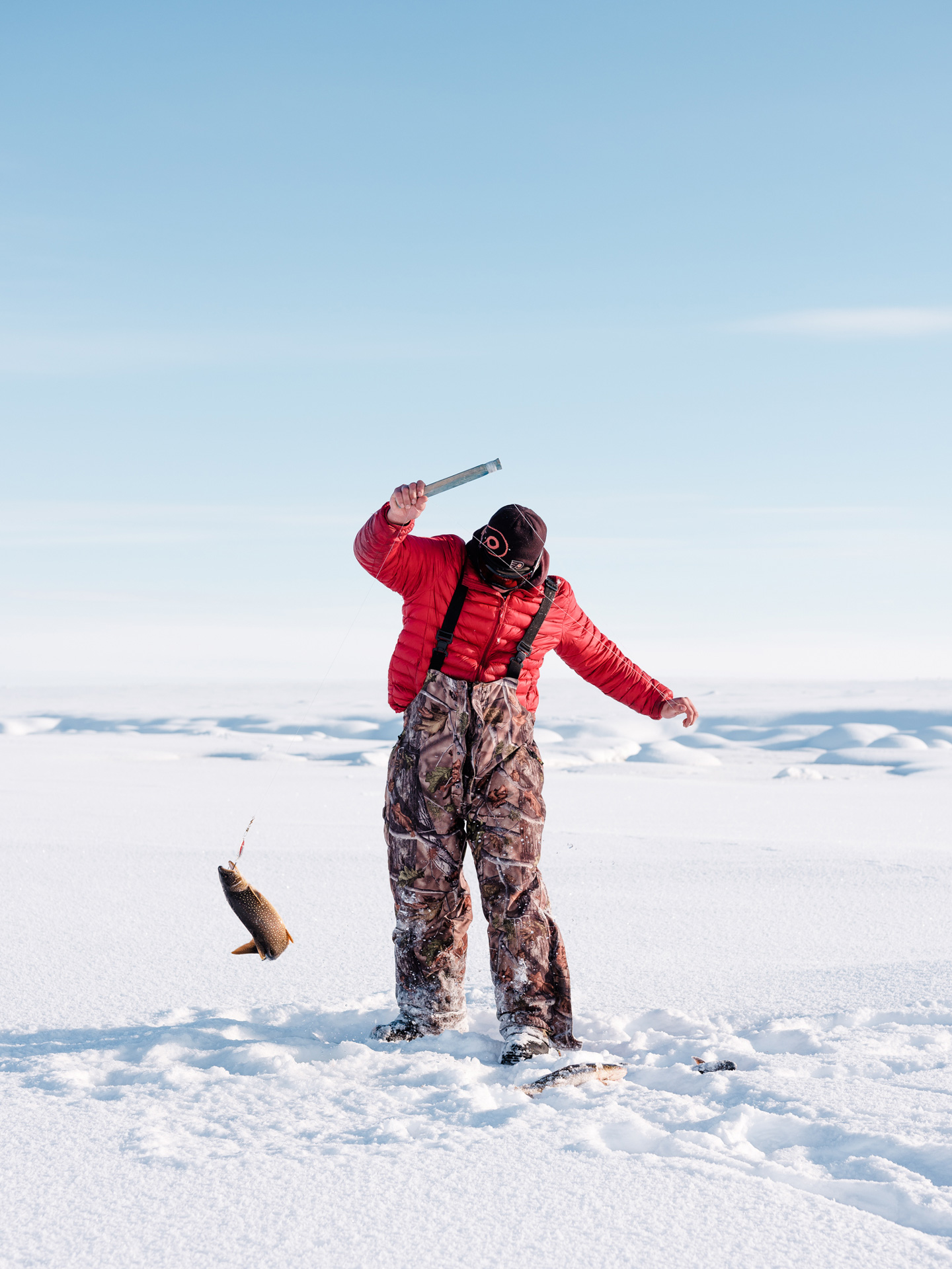 men ice-fishing on lake catching fish in Nunavik by Alexi Hobbs for Air Inuit