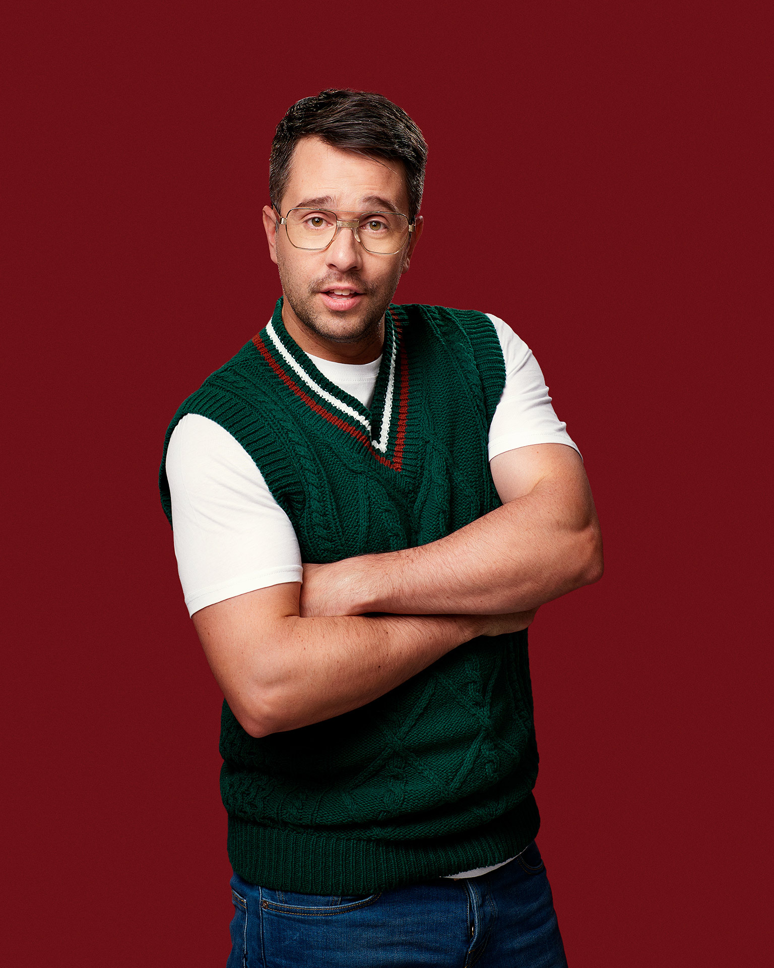 picture of humorist Alexandre Barrette dressed awkwardly in short sleeved white shirt and forest green armless sweater red background for show semi-croquant by Jocelyn Michel