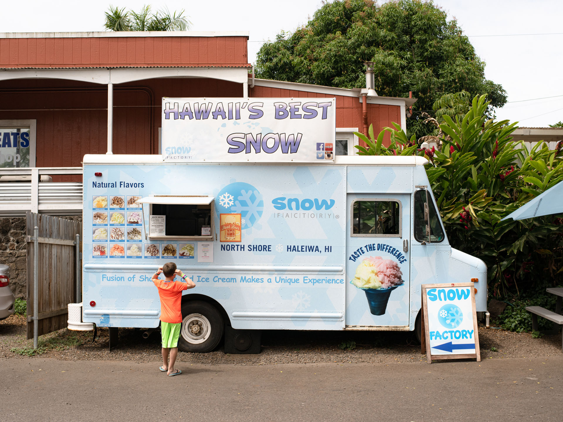 little boy in orange shirt standing in front of food truck selling shave ice snow ice by Alexi Hobbs in Hawai'i for enRoute Magazine