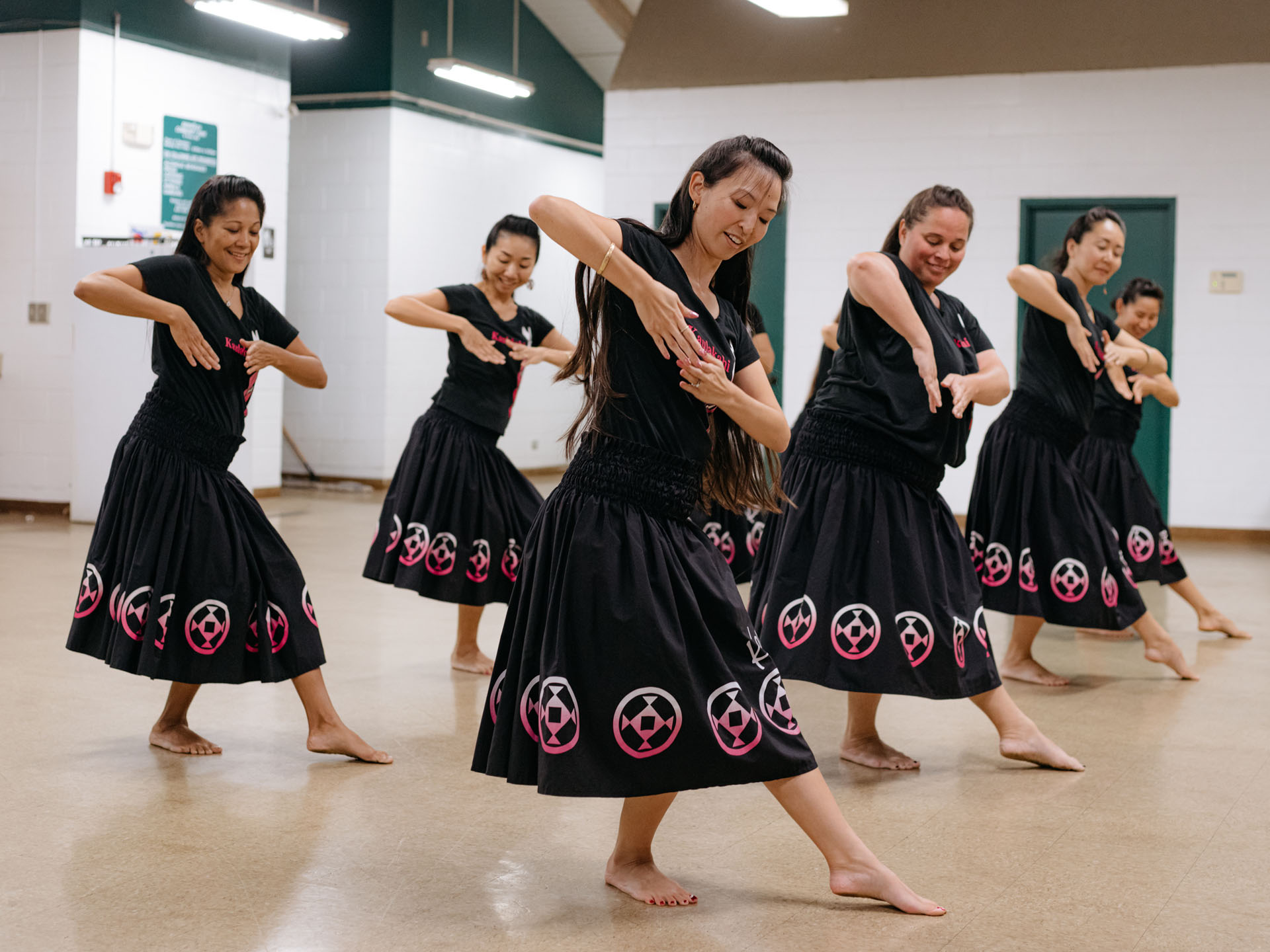 rehearsing group of traditional hula dancers by Alexi Hobbs in Hawai'i for enRoute Magazine