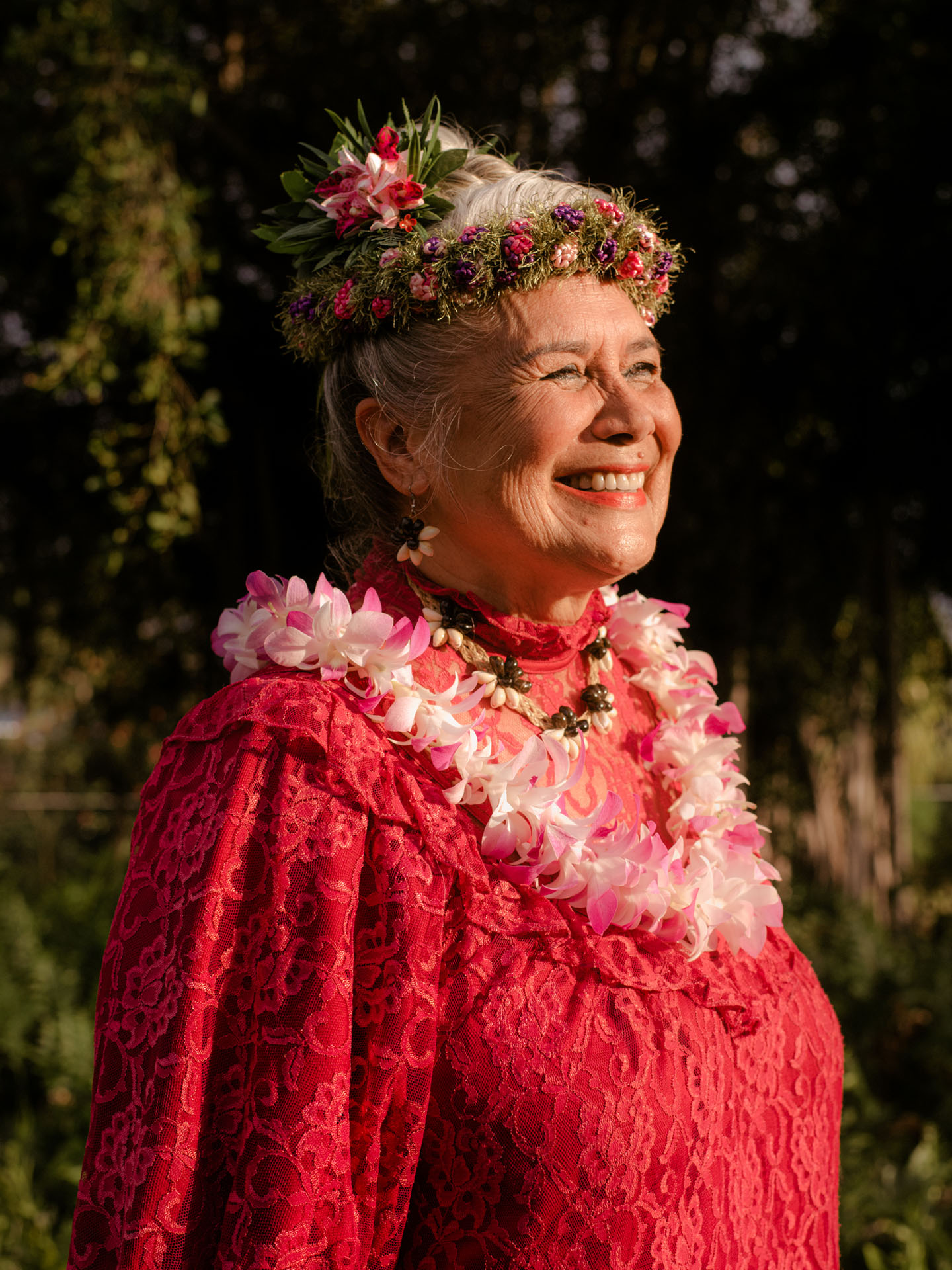 older lady wearing red lace traditional dress flower necklace flower crown smiling in the sun by Alexi Hobbs in Hawai'i for enRoute Magazine