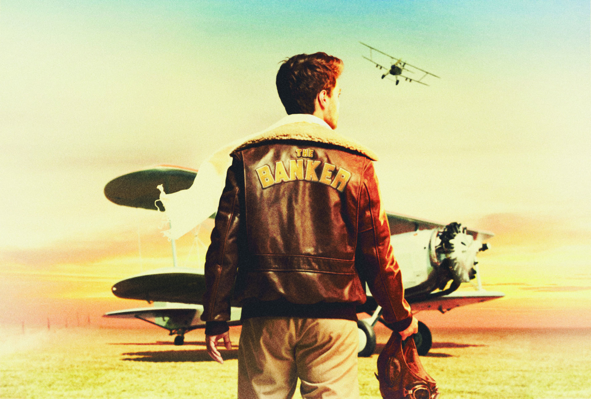 "man from back walking towards airplane in desert wearing brown leather jacket with ""The Banker"" written on the back photographed by Simon Duhamel for bank BNP Paribas"