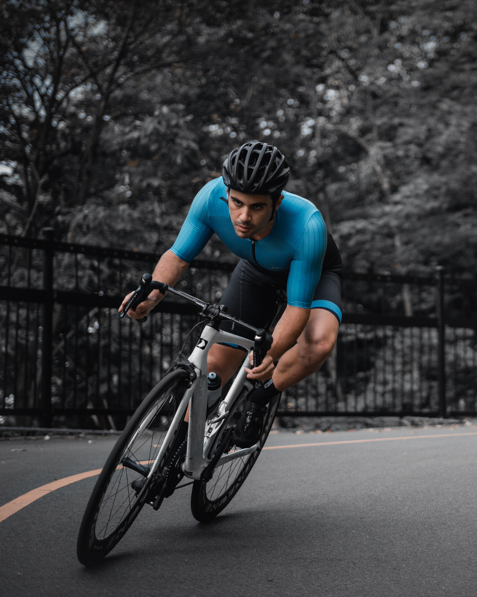 male model wearing black bike helmet and black and blue biking bodysuit biking on road on a white sports bike for Spring Summer 2020 campaign of Louis Garneau with artistic direction and styling by Studio TB