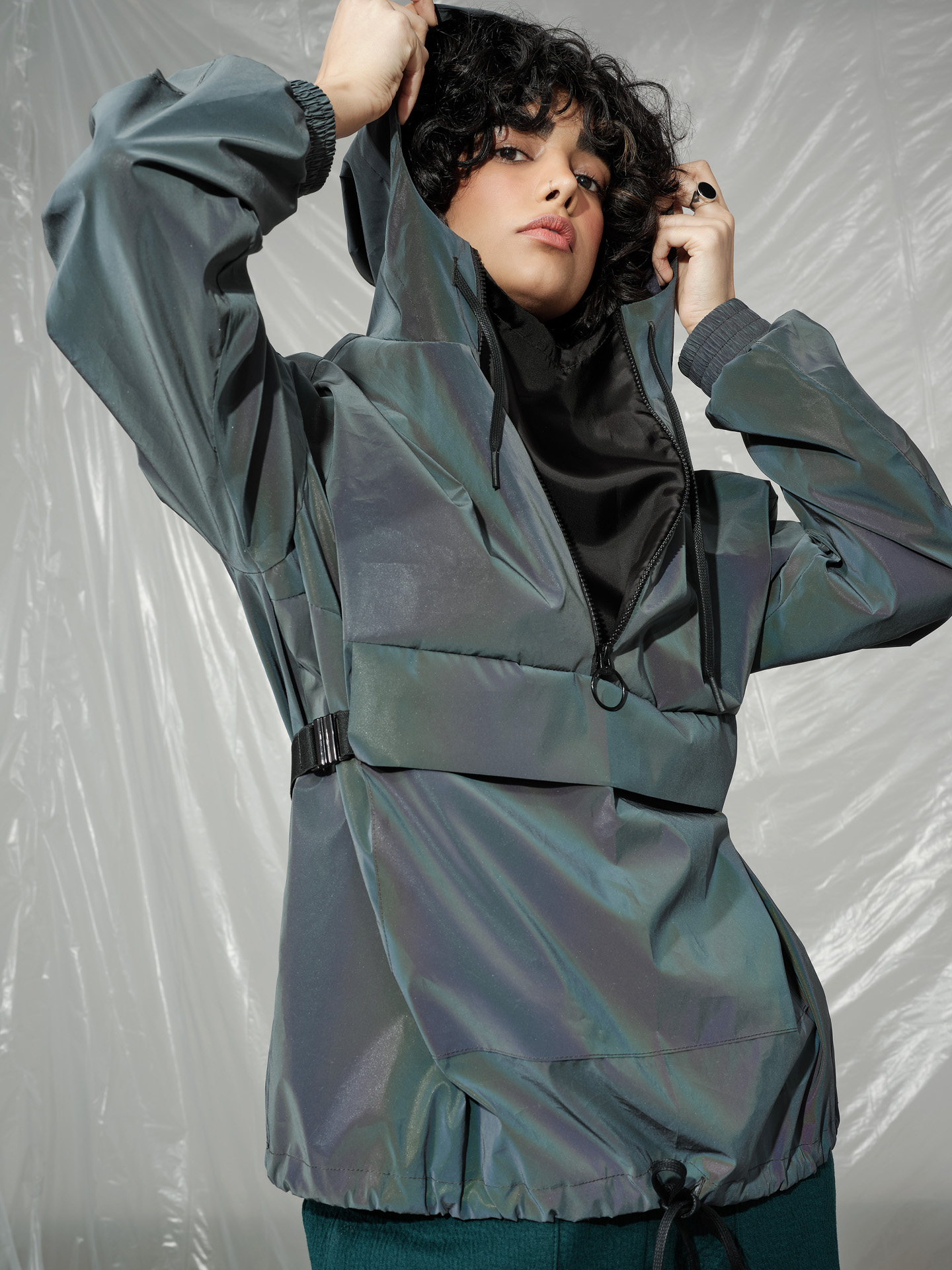 curly haired female model wearing reflective rain jacket looking at camera photographed by Maxyme G Delisle with artistic direction and styling by Studio TB
