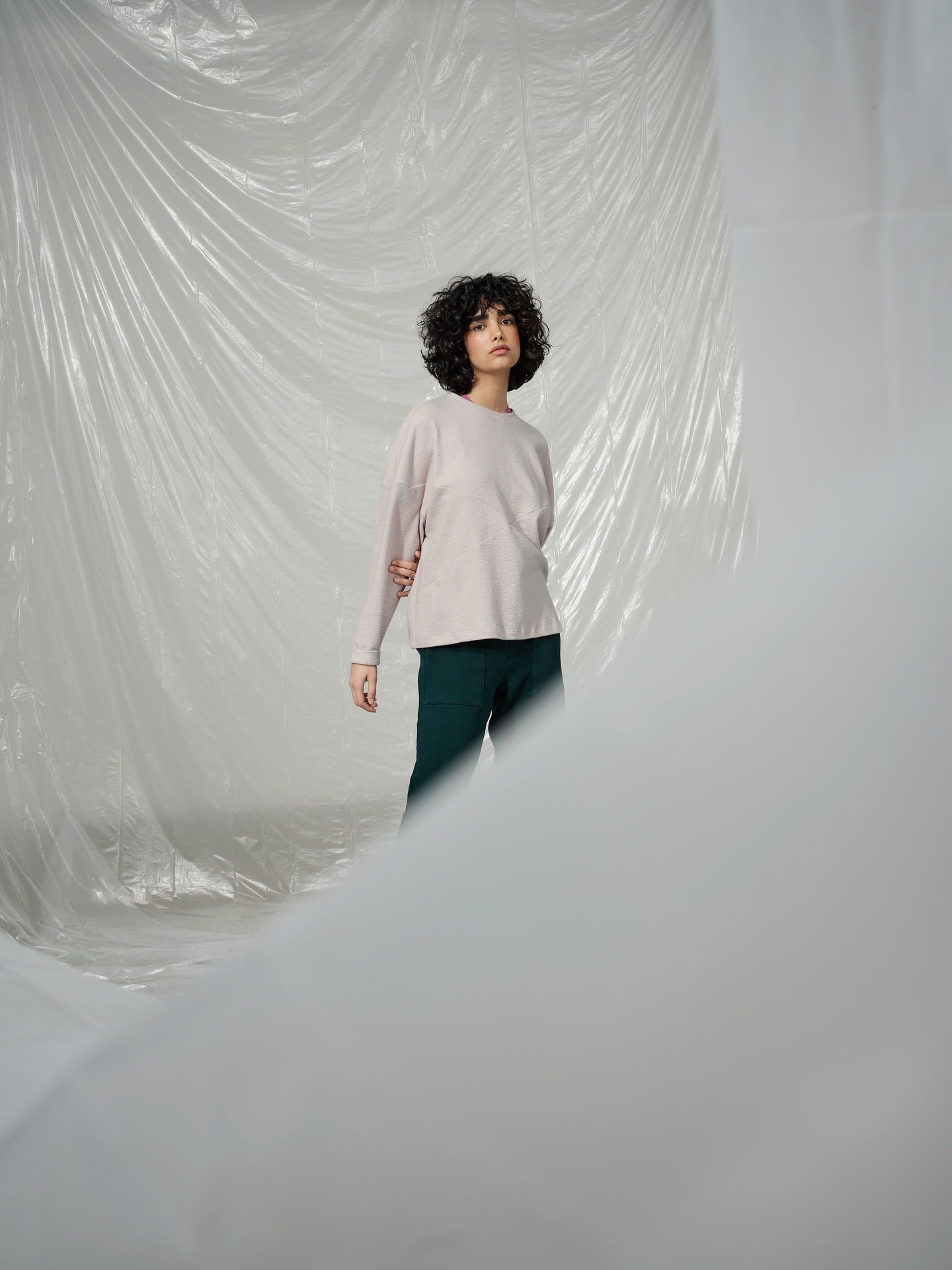 curly haired female model wearing soft pink sweater and dark green pants standing in middle of room covered in plastic construction sheet looking at camera photographed by Maxyme G Delisle with artistic direction and styling by Studio TB