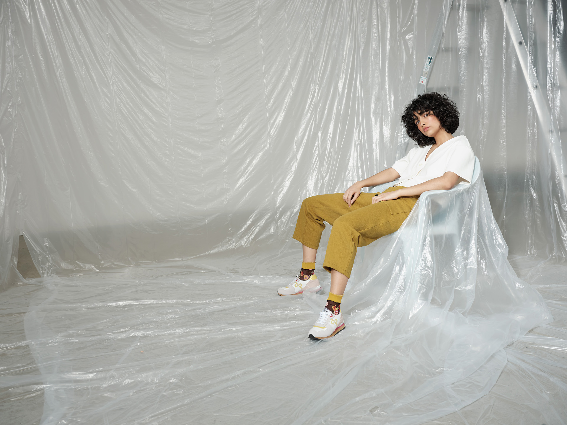 curly haired female model wearing white shirt and mustard pants sitting in plastic chair covered in construction plastic sheet looking at camera photographed by Maxyme G Delisle with artistic direction and styling by Studio TB