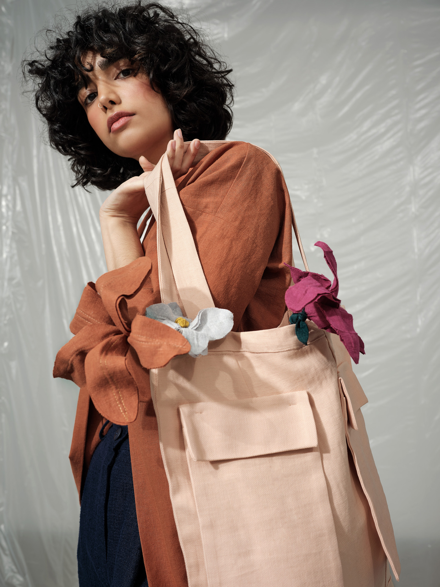 curly haired female model wearing brown jacket tight white crop top and baggy dark blue pants holding soft pink tote bag over her shoulder looking at camera photographed by Maxyme G Delisle with artistic direction and styling by Studio TB
