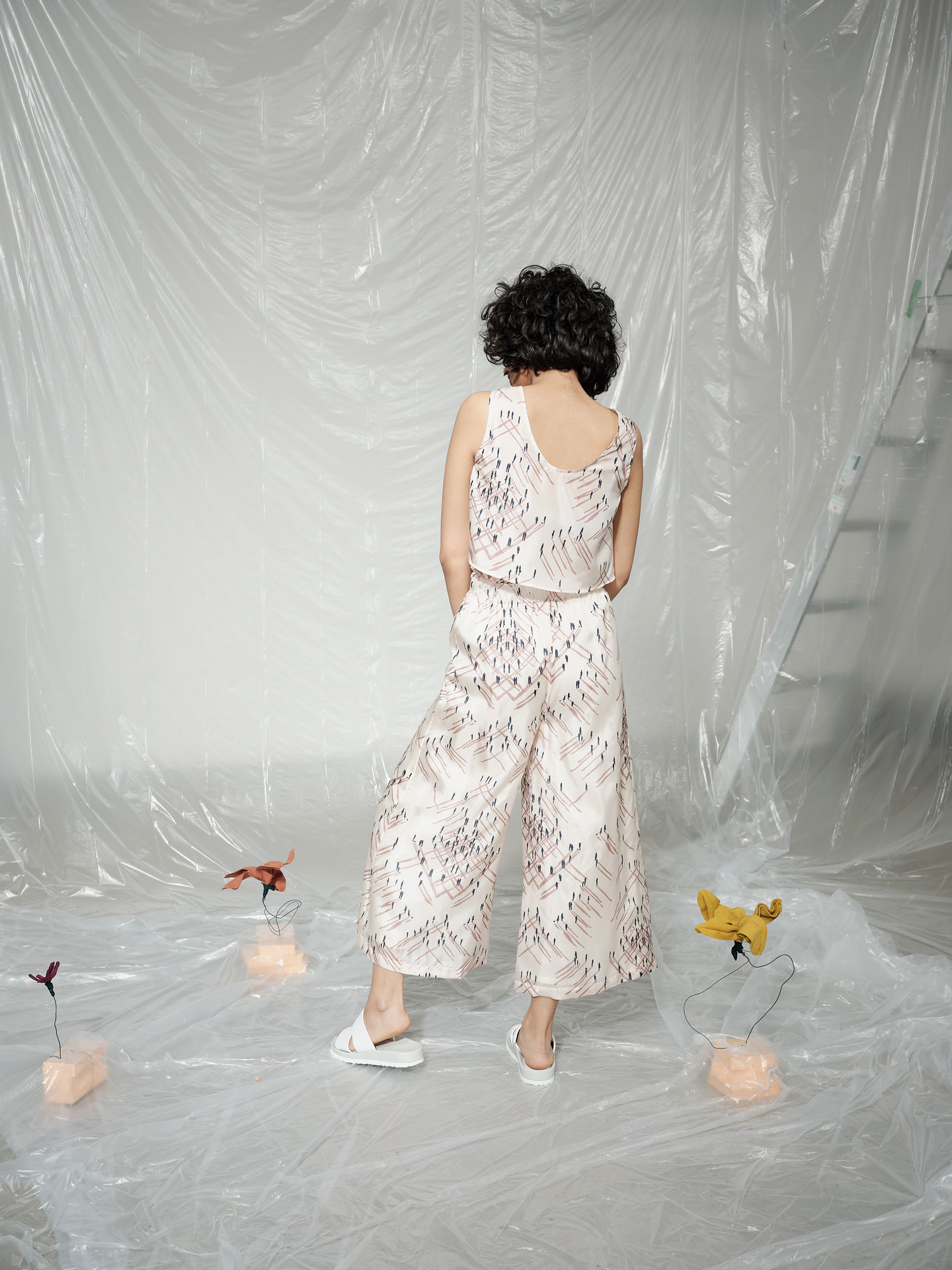 curly haired female model wearing people-printed in blue and soft pink on white fabric ensemble standing from back in room covered in plastic construction sheet looking at camera photographed by Maxyme G Delisle with artistic direction and styling by Studio TB