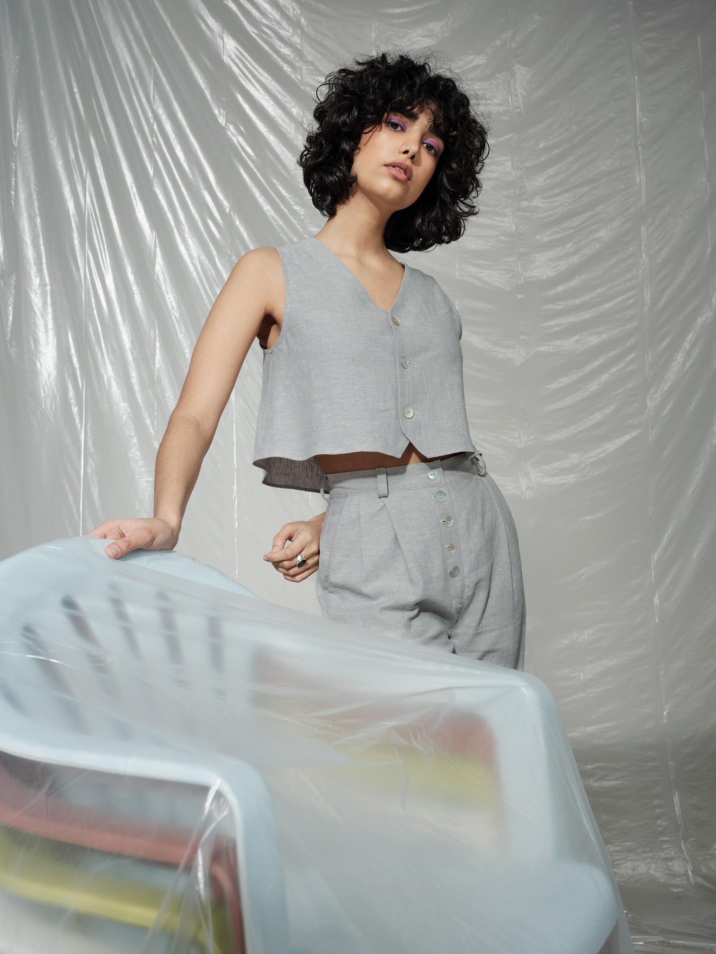 curly haired female model wearing grey linen ensemble standing next to stack of colorful plastic chairs covered in plastic construction sheet looking at camera photographed by Maxyme G Delisle with artistic direction and styling by Studio TB