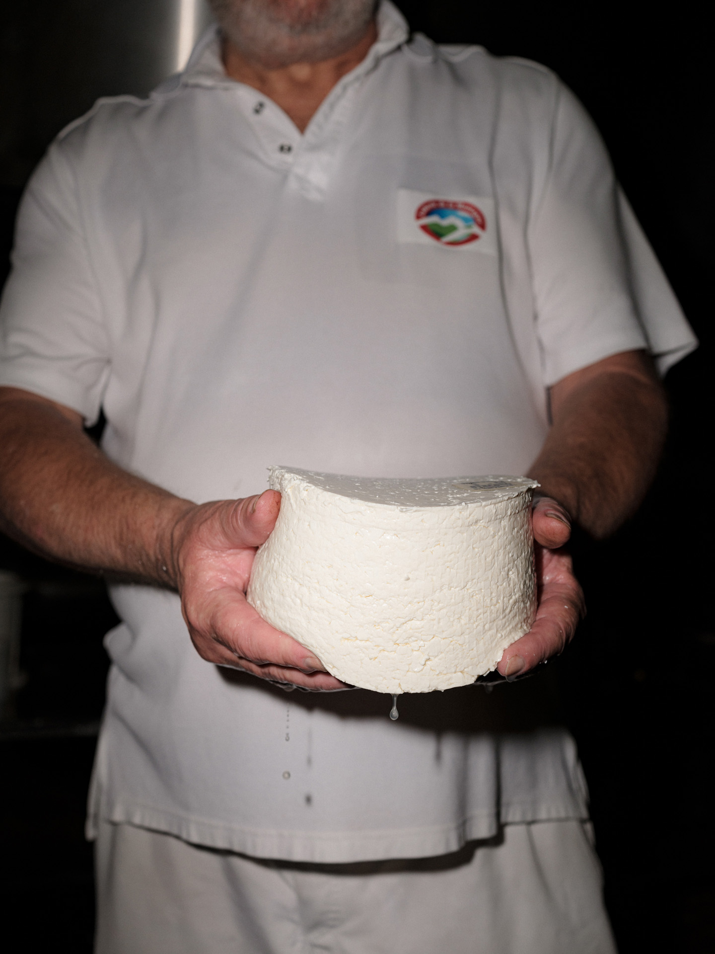 cheese maker holding freshly unmolded goat cheese by Alexi Hobbs in Auvergne for Reflets de France