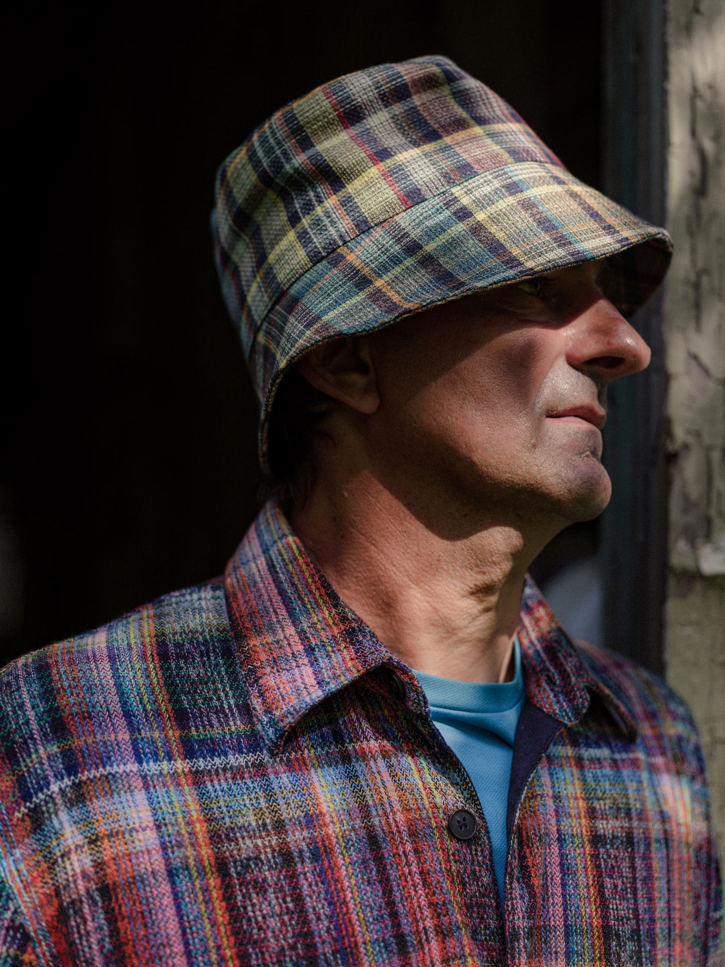 man in colourful plaid overalls standing in door frame with shadows of tree branches on his face wearing a low bob hat by Alexi Hobbs at Pinard & Filles winery for Larose Paris