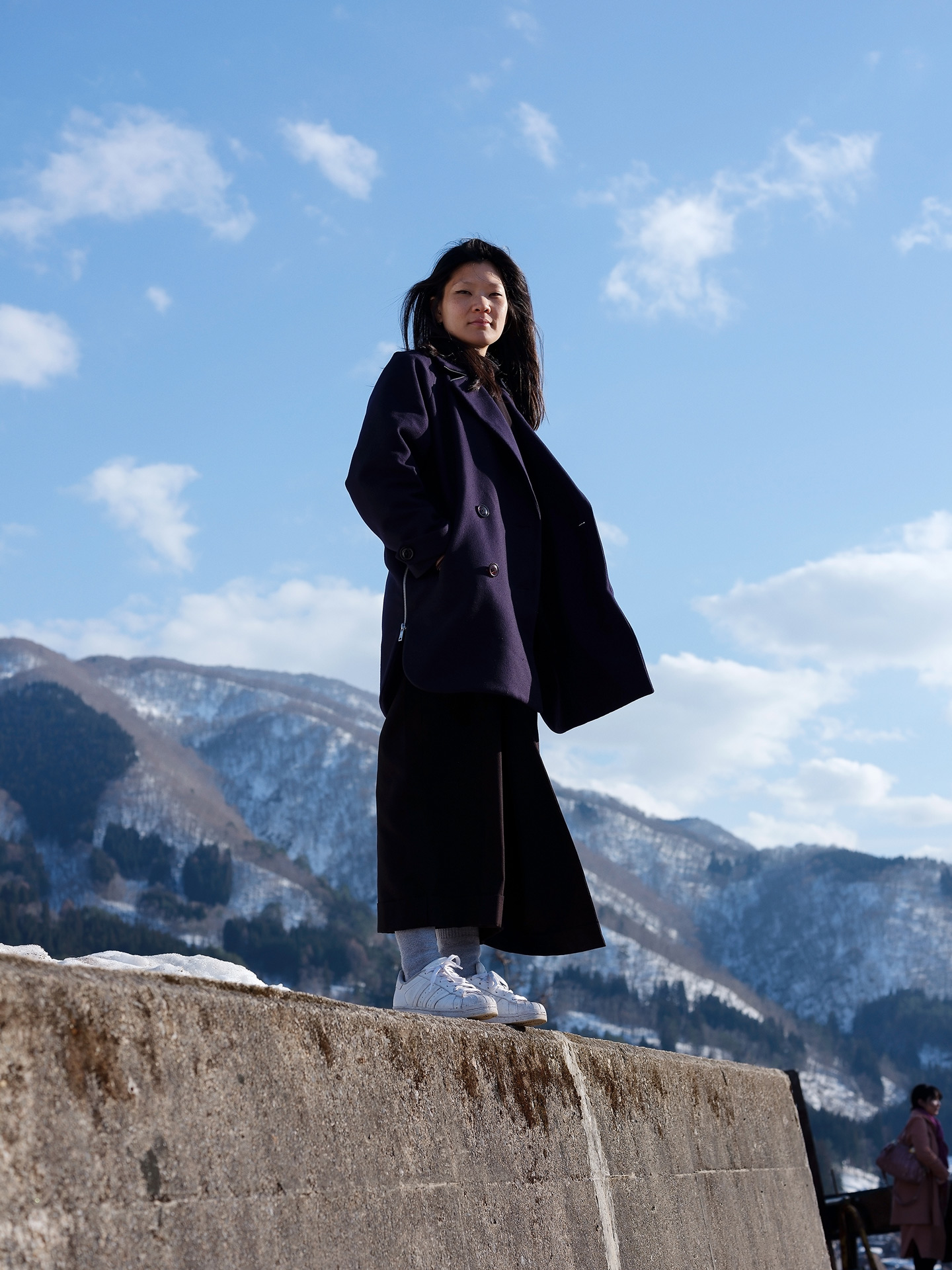 asian woman Shammy posing on cement block against blue sky in Hong Kong Japan by Guillaume Simoneau