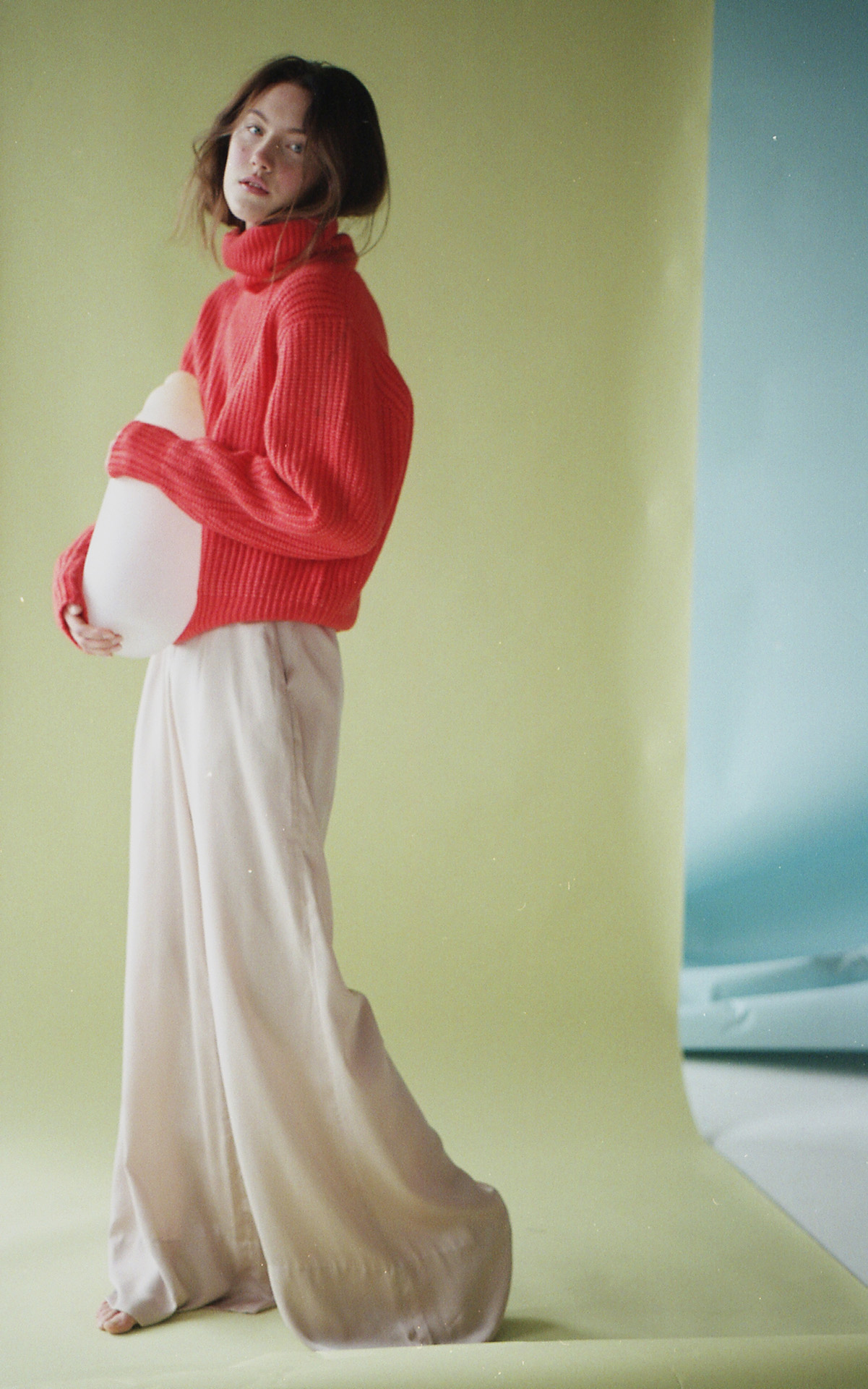 female model Jana standing on light green paper background holding white vase against her wearing red knit turtleneck sweater and large white pants barefoot looking at camera photographed by Naomie from Studio TB for project Sculpting Jana