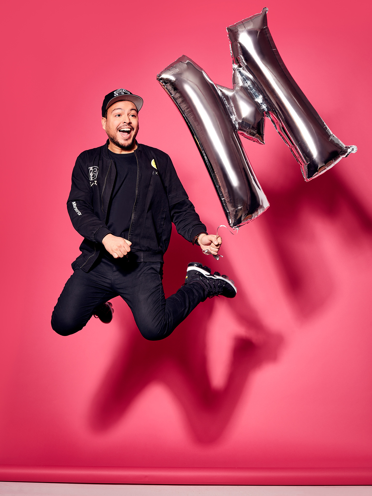 portrait of Mehdi jumping in the air with silver M balloon pink background by Jocelyn Michel for Journal de Montréal