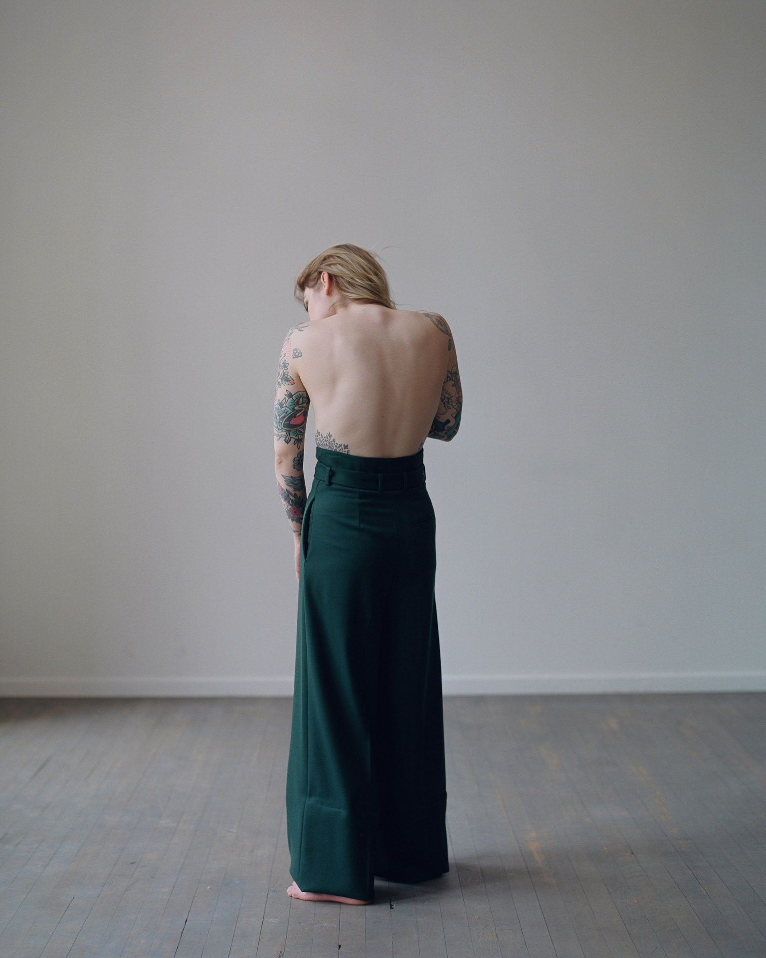 Coeur de Pirate turned around showing her bare back wearing large forest green pants by Maxyme G Delisle for Loulou Magazine