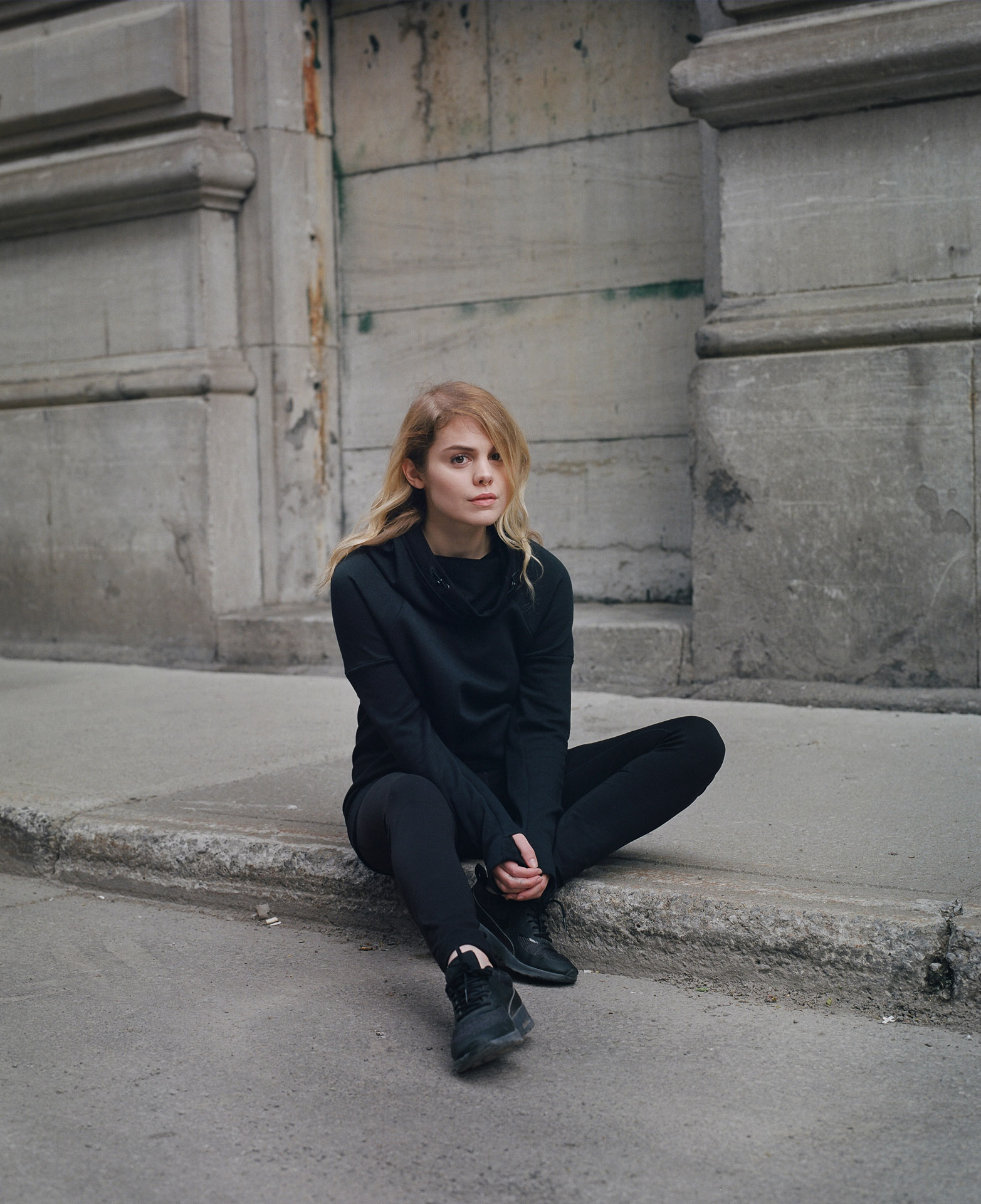 singer Coeur de Pirate sitting in the street no makeup wearing all black knit wear with black sneakers looking at camera by Maxyme G Delisle for Loulou Magazine