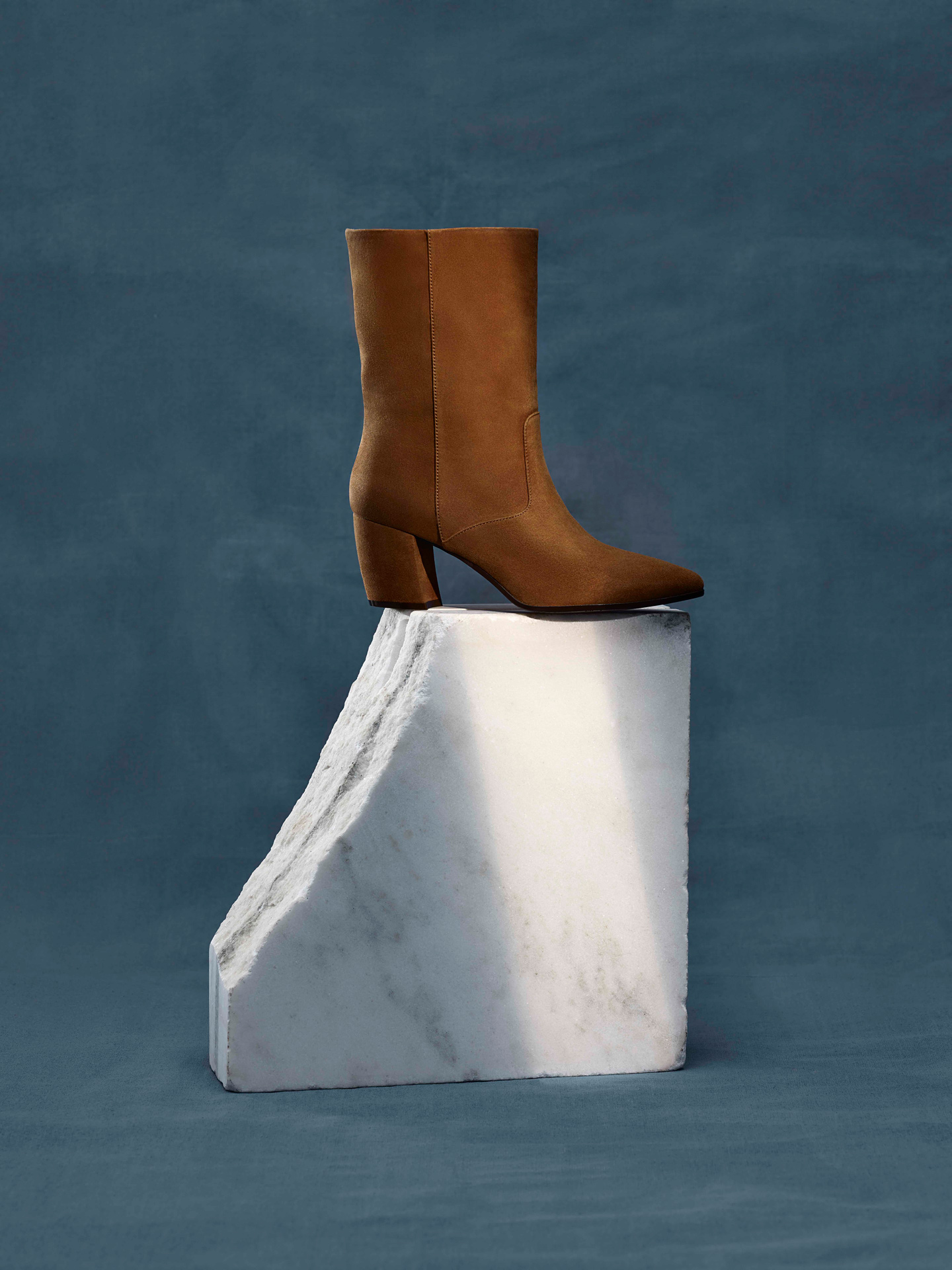 brown suede boot on piece of white marble on blue background by Maxyme G Delisle with artistic direction from Studio TB for Jean-Paul Fortin Fall collection