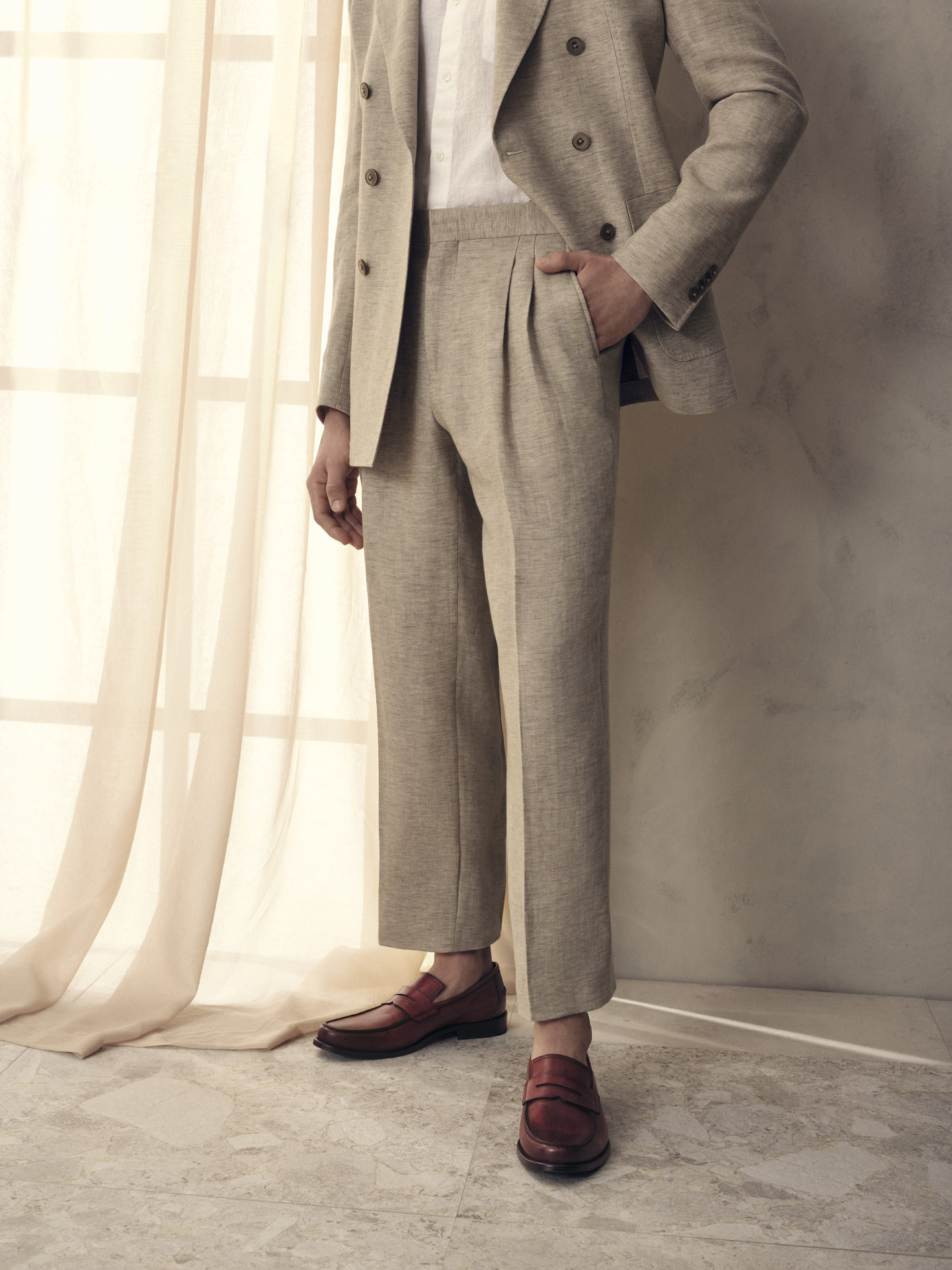 male model wearing natural colored linen suit with deep red leather loafers for Jean-Paul Fortin summer-spring collection photographed by Maxyme G Delisle with artistic direction, conception and set design by Studio TB