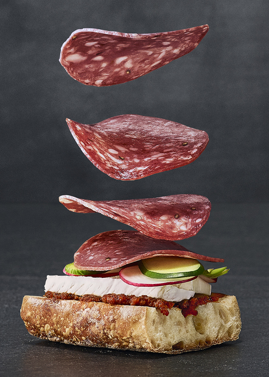 close up of salami slices falling softly on bread with tomato spread brie cheese and vegetables by Mathieu Levesque for Fantino and Mondello Rethink