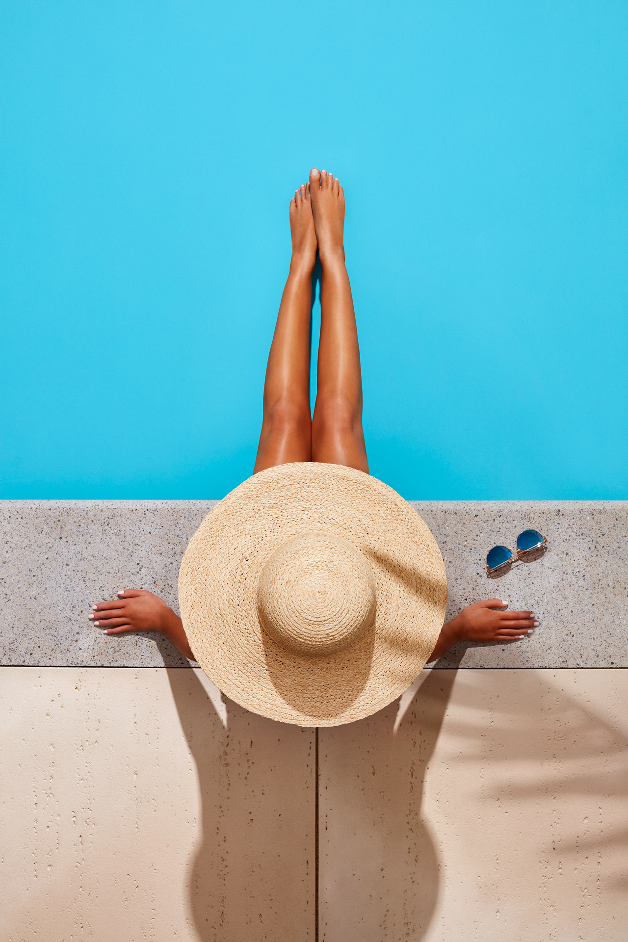 top view of woman sitting on pool side wearing big hat by Mathieu Levesque for Techo Bloc