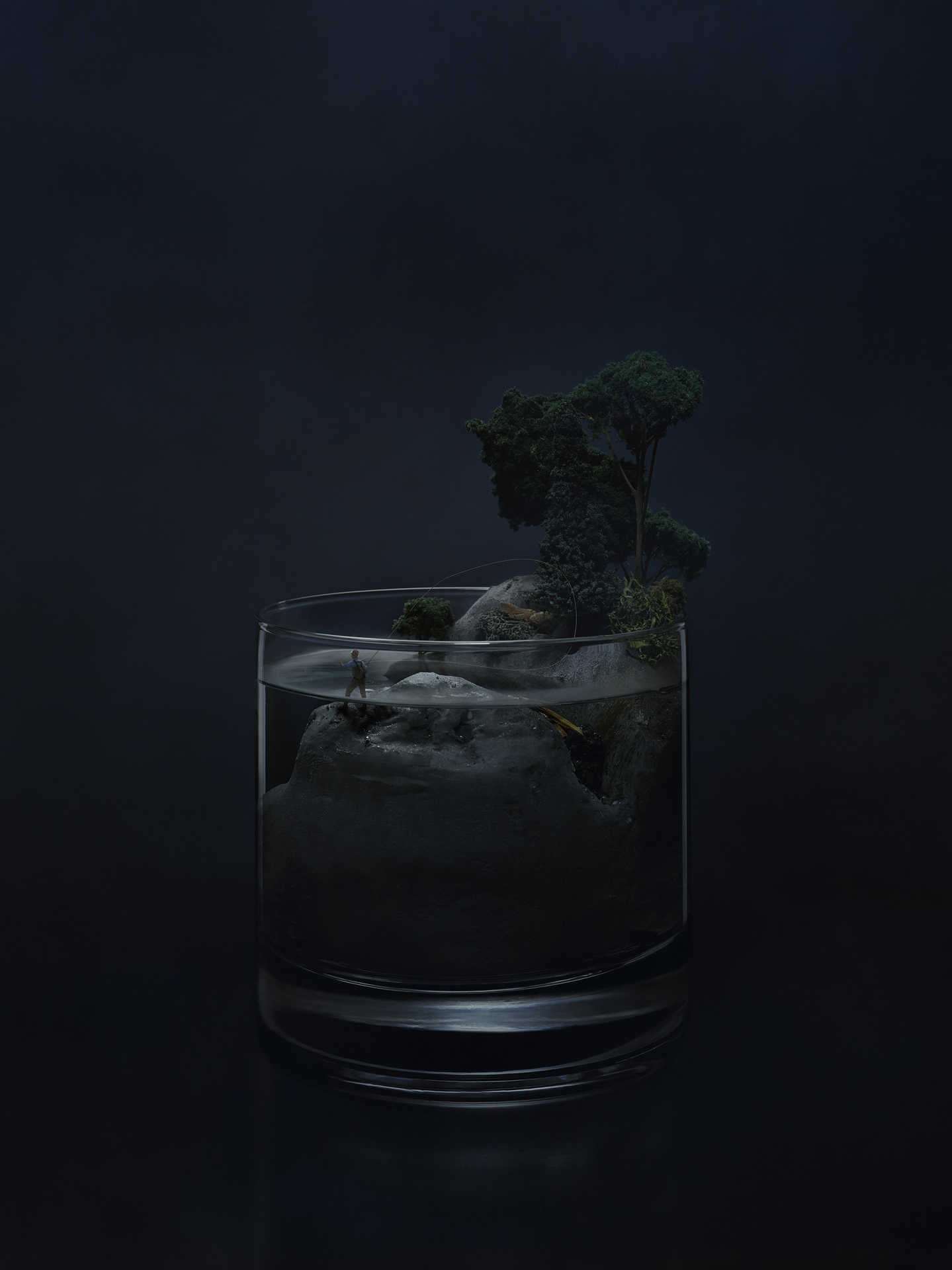 glass of alcohol with miniature scenery of grey rocks big tree and a fisherman on dark blue background by Mathieu Levesque